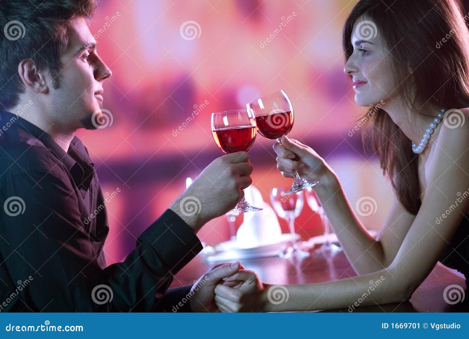 Jeunes couples partageant une glace de vin rouge dans le restaurant, celebrat