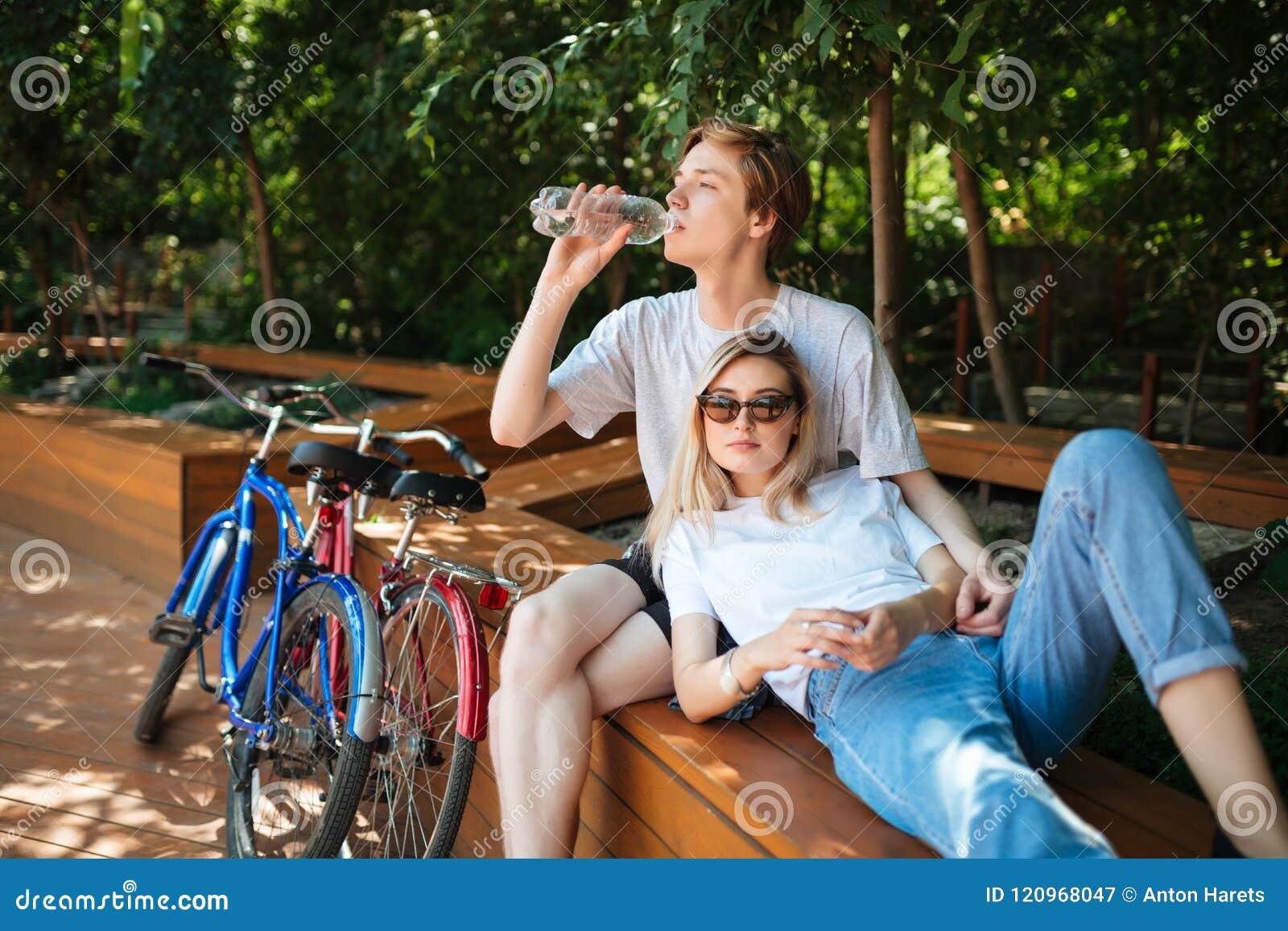Jeunes couples passant le temps sur le banc en bois en parc avec deux bicyclettes tout près Garçon s asseyant sur le banc et l ea
