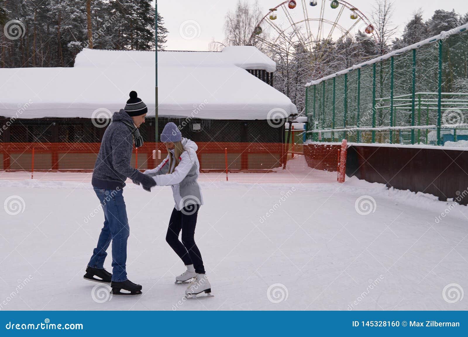 Jeunes couples patinant ? une piste de patinage publique de glace dehors dans la ville