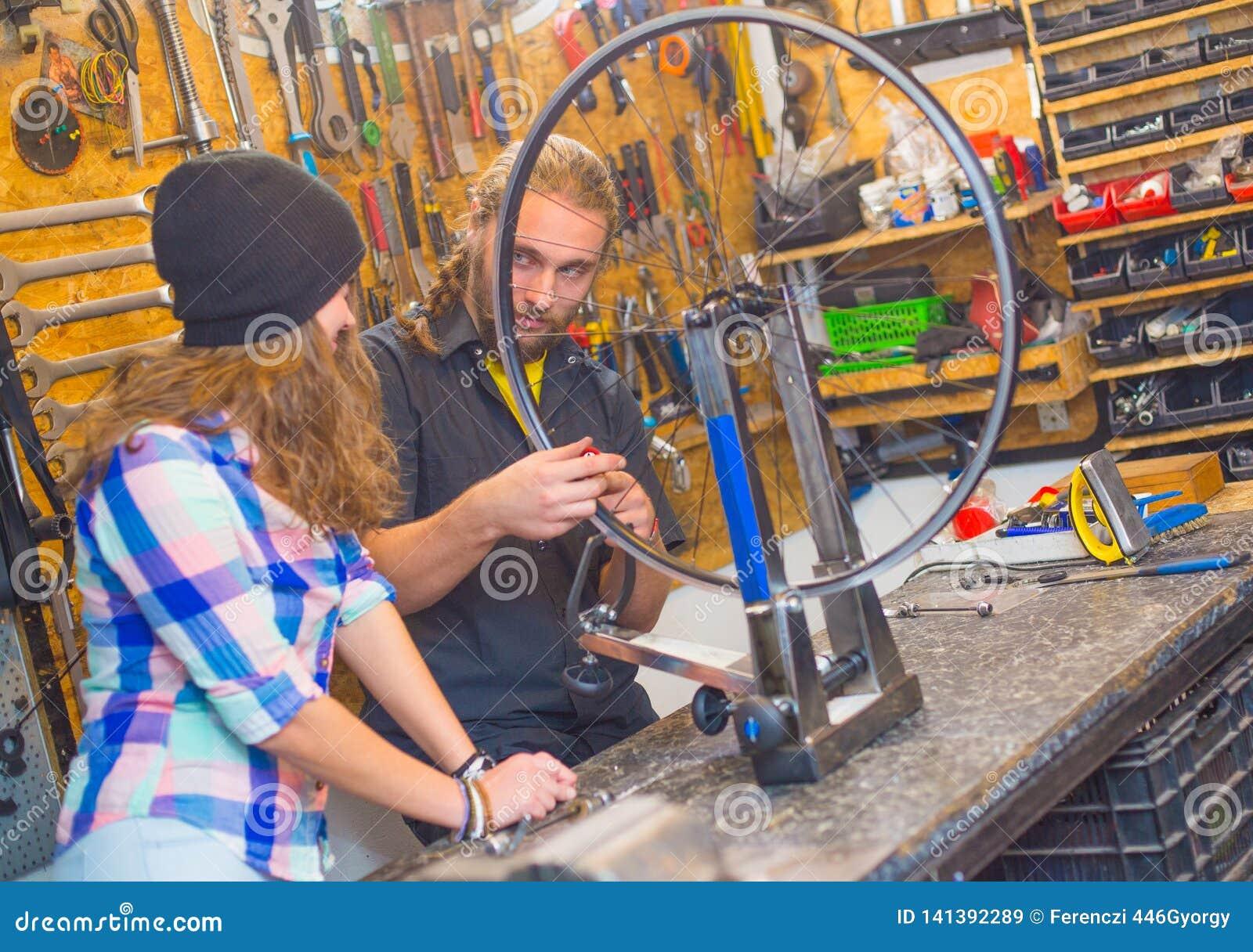 Jeunes couples réparant la bicyclette dans l atelier