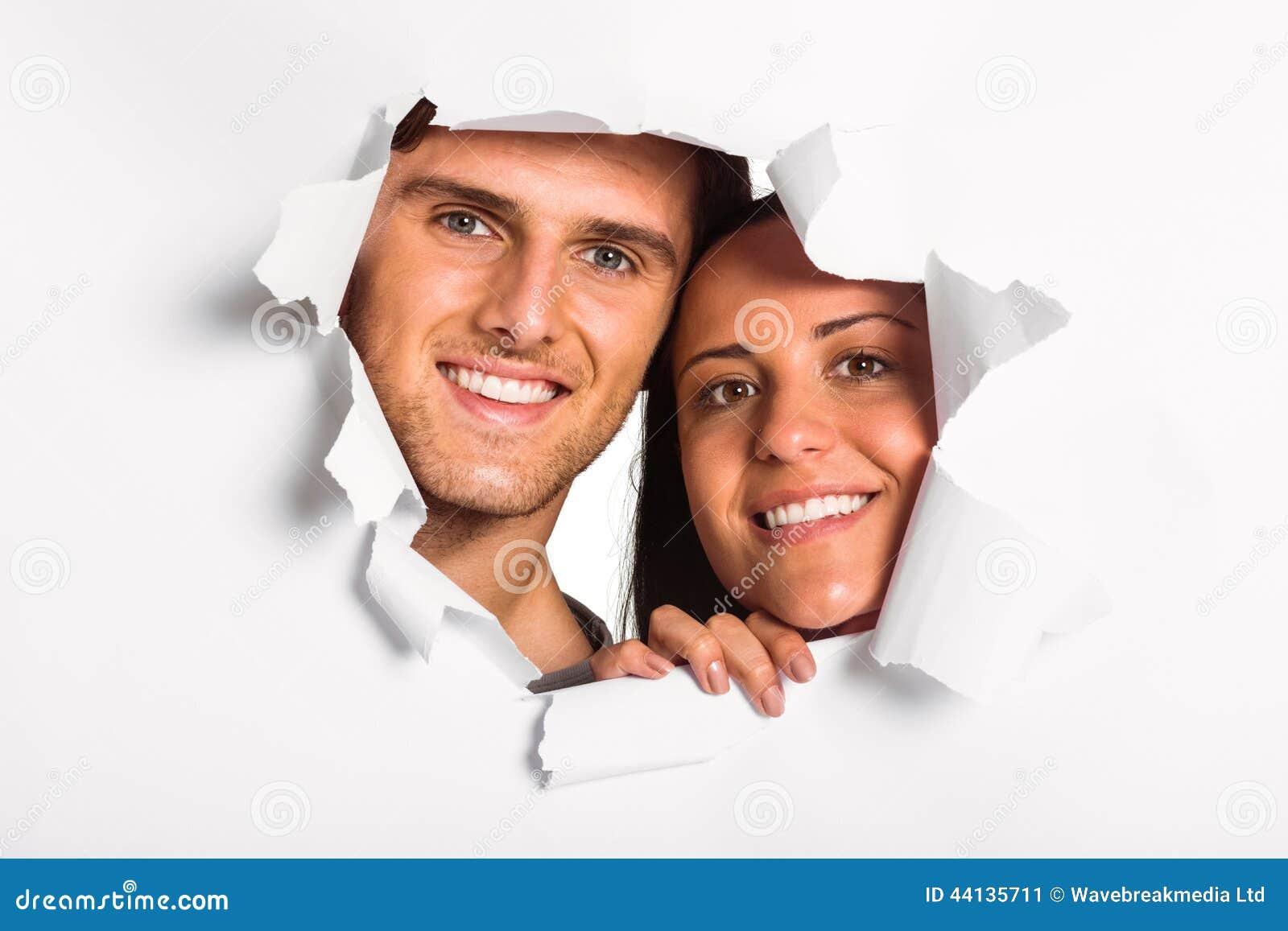 Jeunes couples regardant par la déchirure de papier
