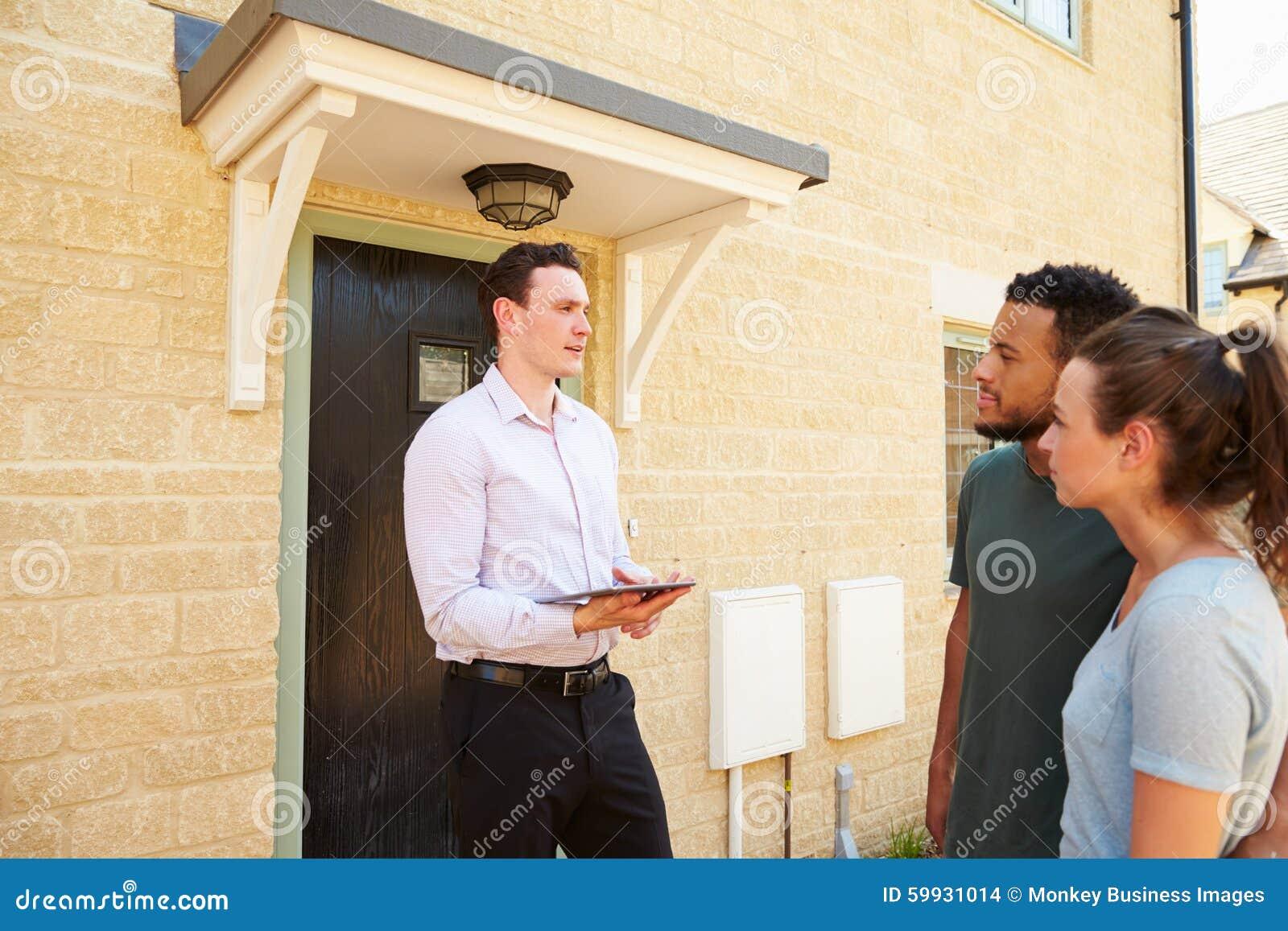 Jeunes couples regardant une maison avec le vrai agent immobilier masculin