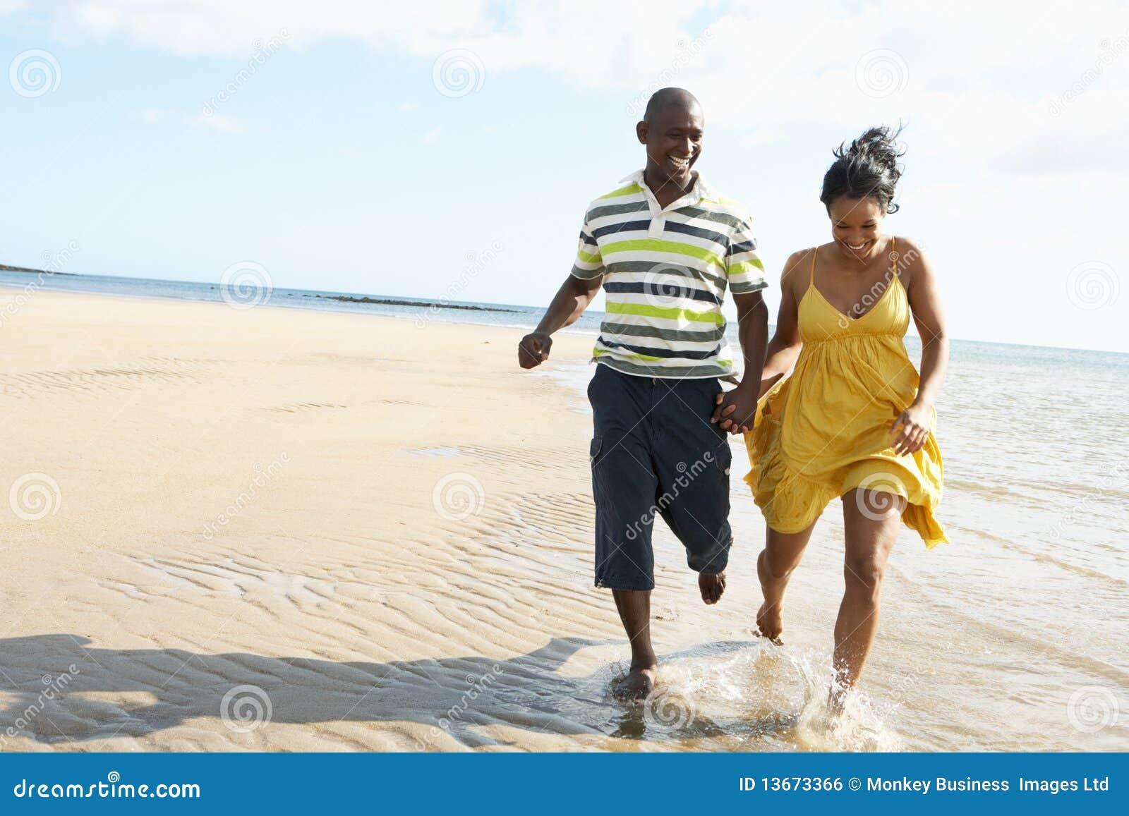 Jeunes couples romantiques fonctionnant le long du rivage
