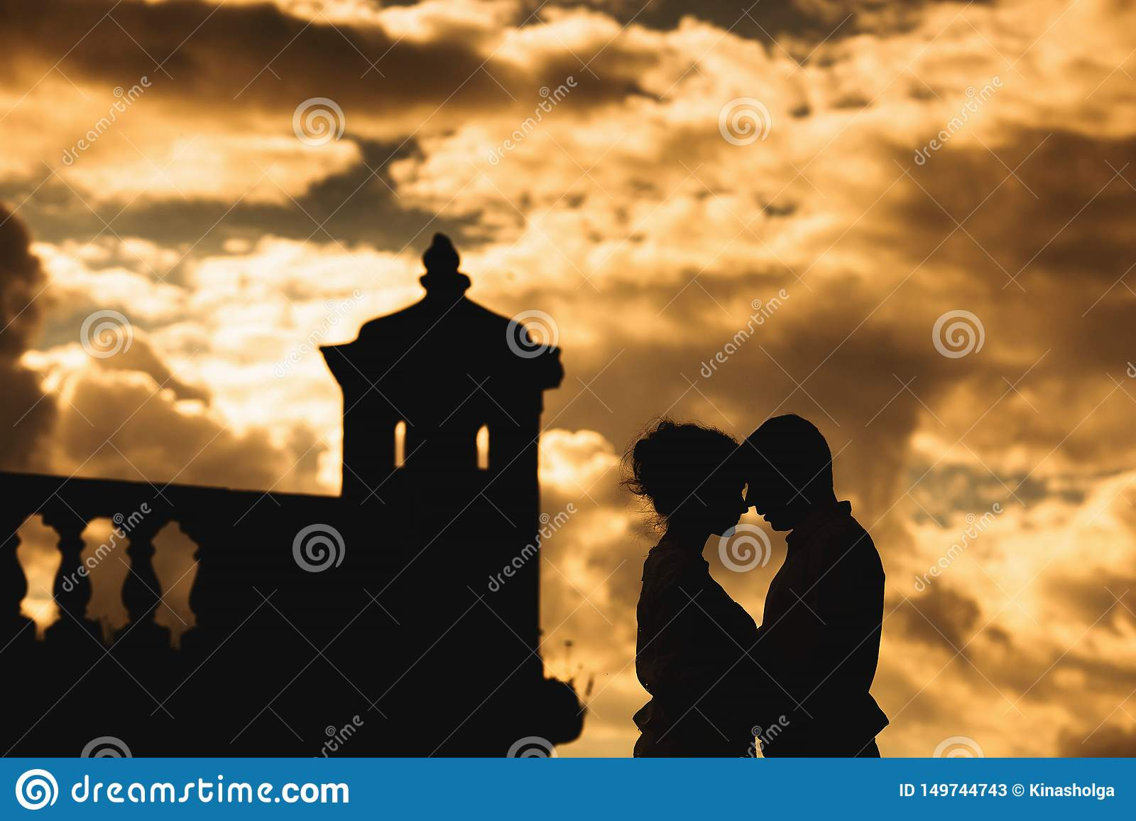 Jeunes couples romantiques sur le mur de forteresse au coucher du soleil