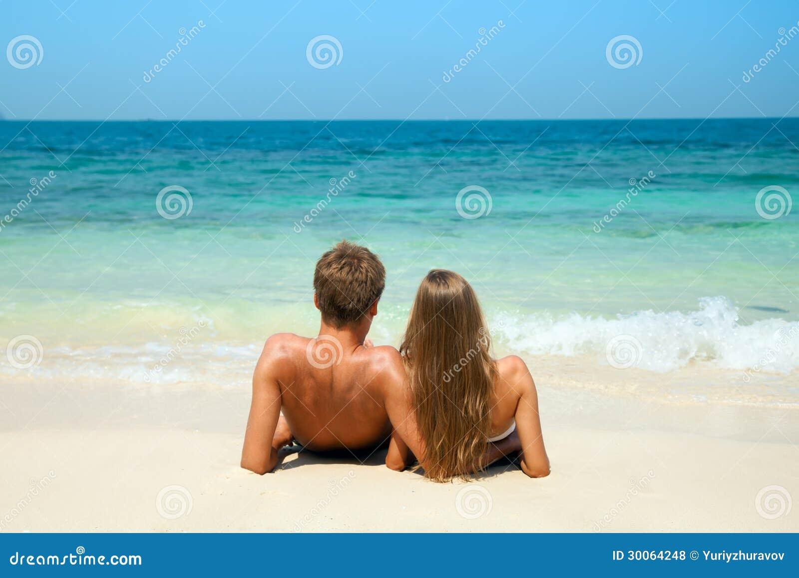 Jeunes couples se reposant ensemble sur un sable par la mer