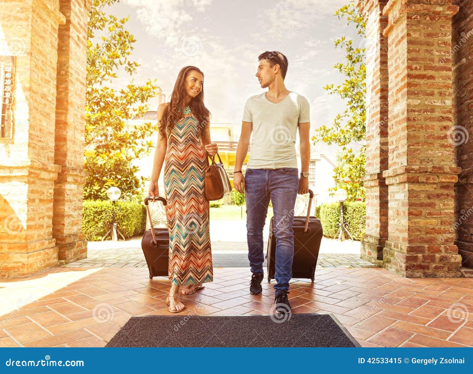 Jeunes couples se tenant au couloir d hôtel sur l arrivée, recherchant la pièce, tenant des valises
