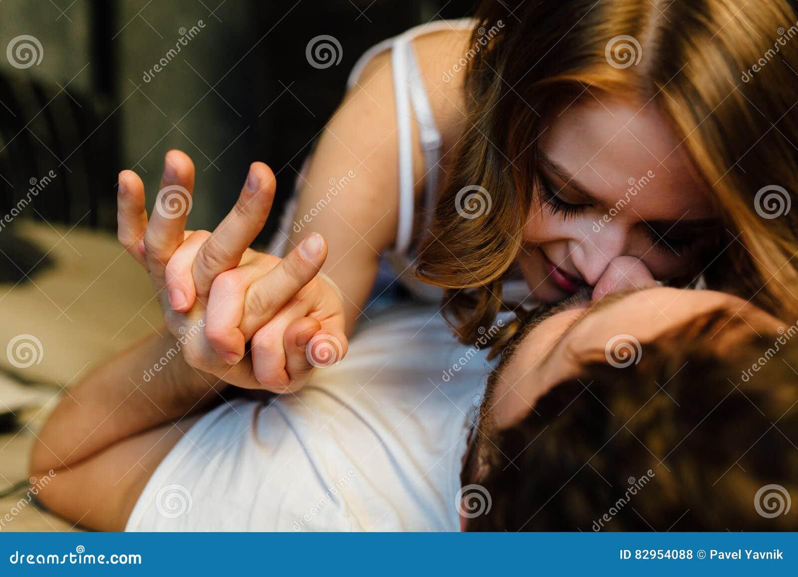 Jeunes couples sexy dans l amour se situant dans le lit dans l hôtel, embrassant sur les feuilles blanches, fin