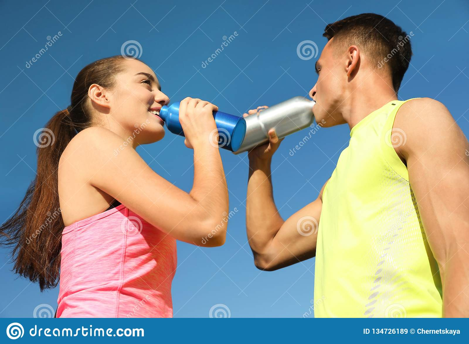 Jeunes couples sportifs buvant des bouteilles d eau contre le ciel bleu