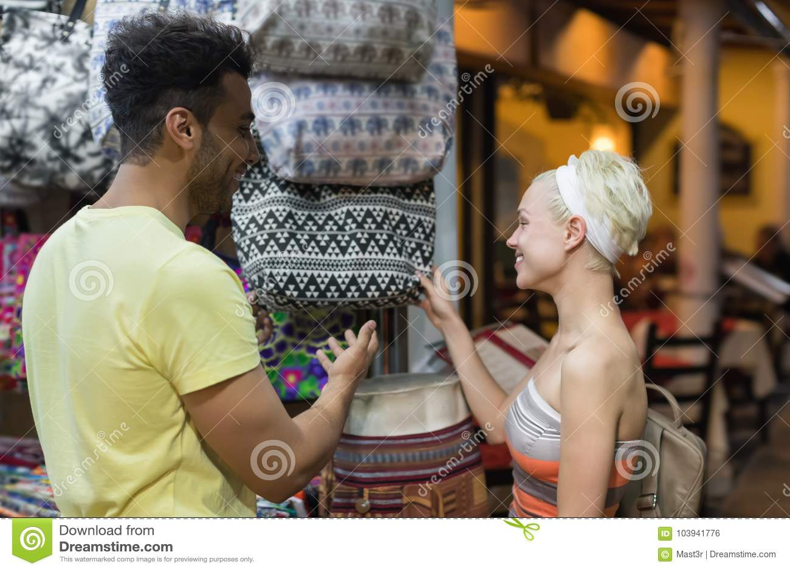 Jeunes couples sur des achats choisissant le sourire heureux de sac, d homme et de femme dans le magasin de détail