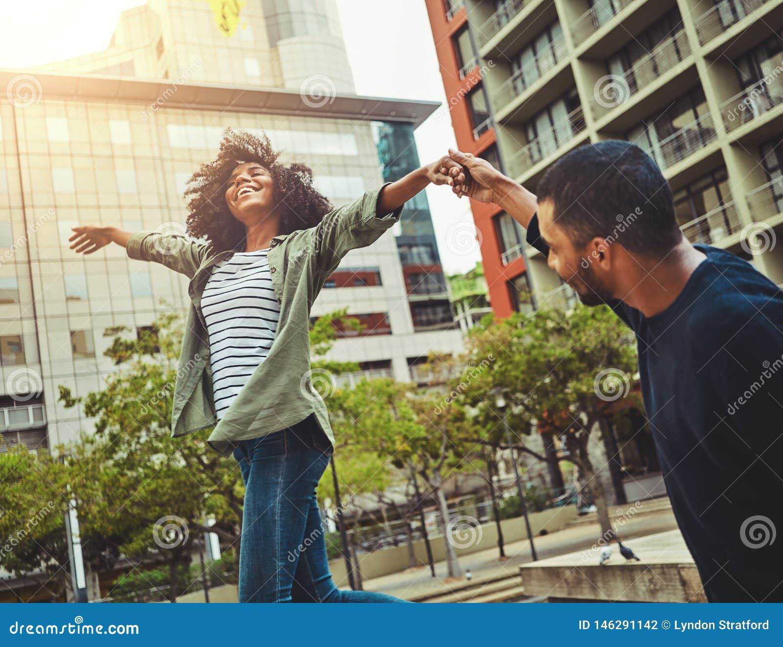 Jeunes couples tenant des mains appréciant dans la ville