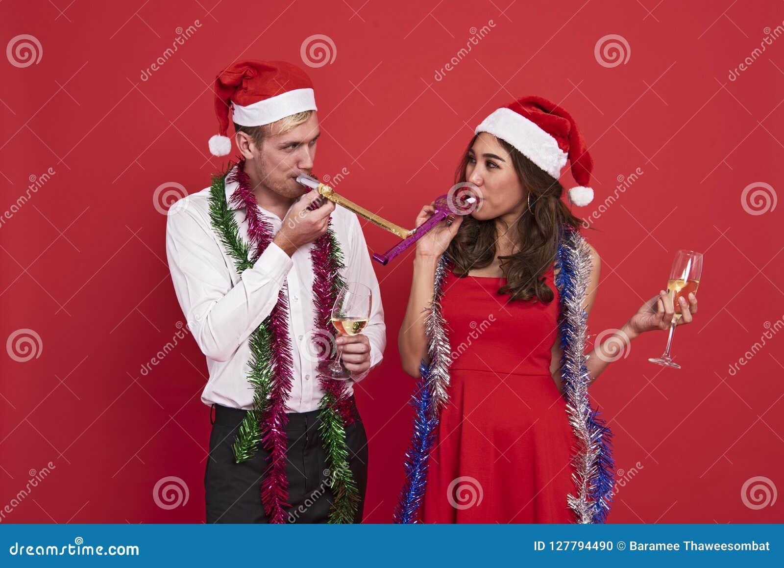Jeunes couples tenant des verres de champagne et soufflant la célébration de sifflements de partie