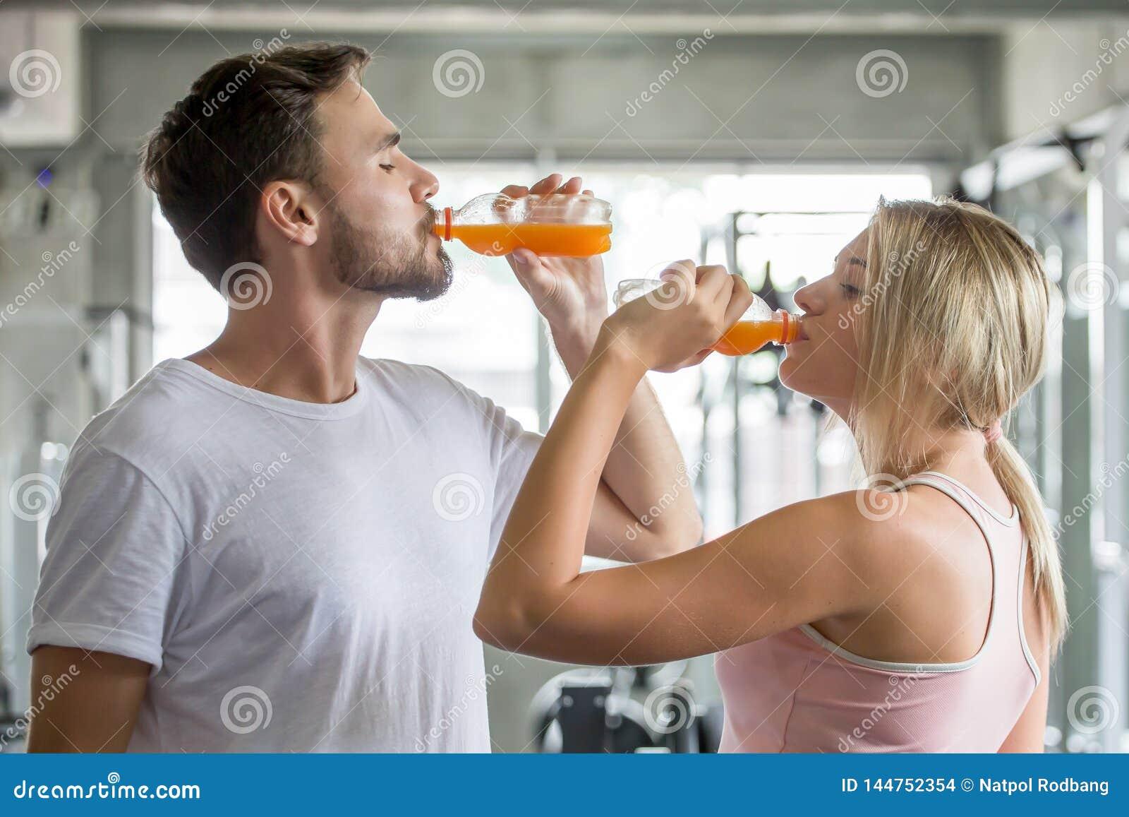 Jeunes de forme physique de couples buvant des bouteilles de jus d orange dans le gymnase sports homme et exercices de femme