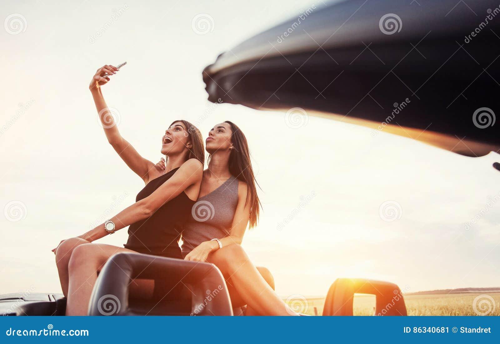 Jeunes deux femmes à une séance photos Filles posant heureusement