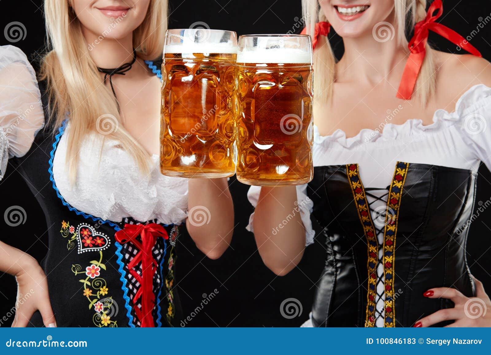 Jeunes et belles filles bavaroises avec deux tasses de bière sur le fond noir