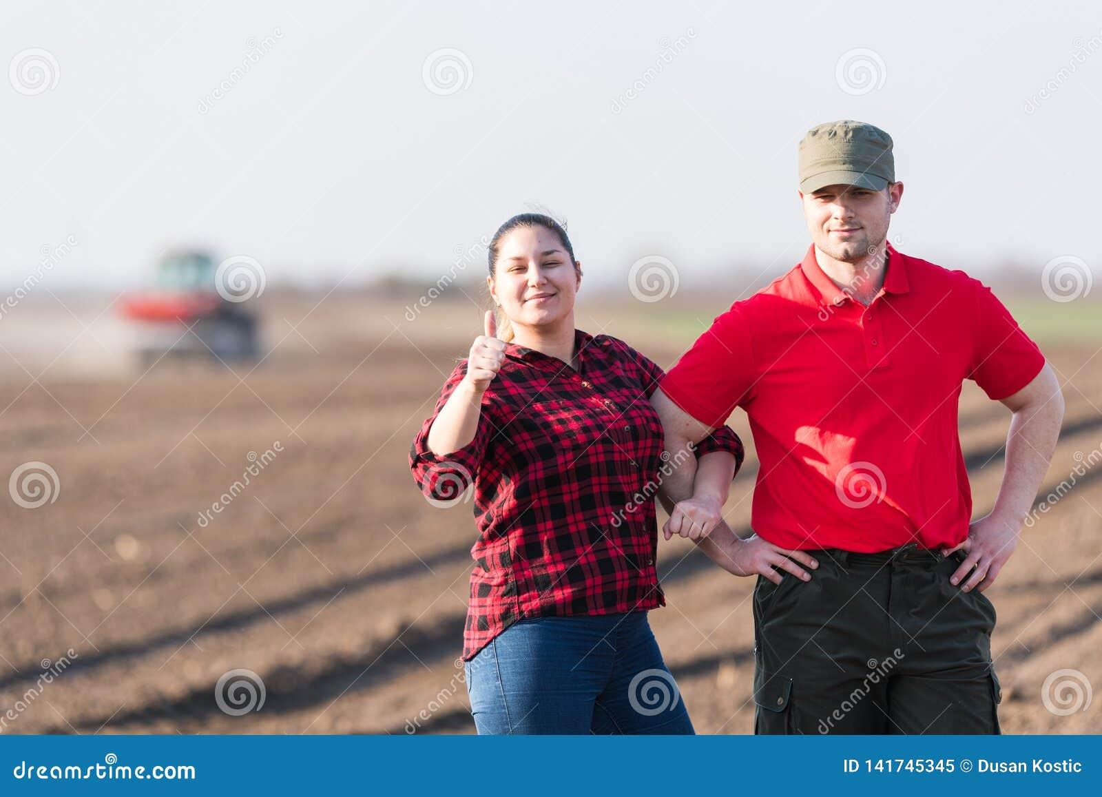 Jeunes exploitants agricoles examing les champs de bl? plant?s