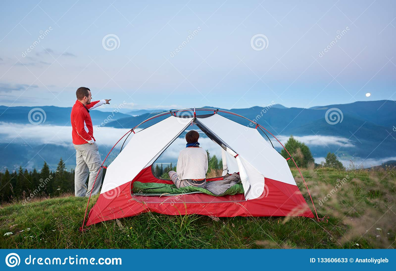 Jeunes expositions masculines de touristes loin pour musarder son compagnon femelle en montagnes à l aube