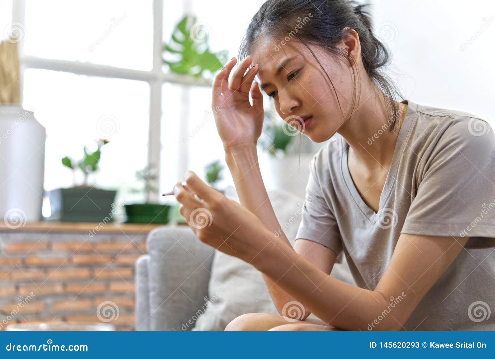 Jeunes femmes asiatiques sur la douleur de sofa du mal de tête et avoir une certaine fièvre