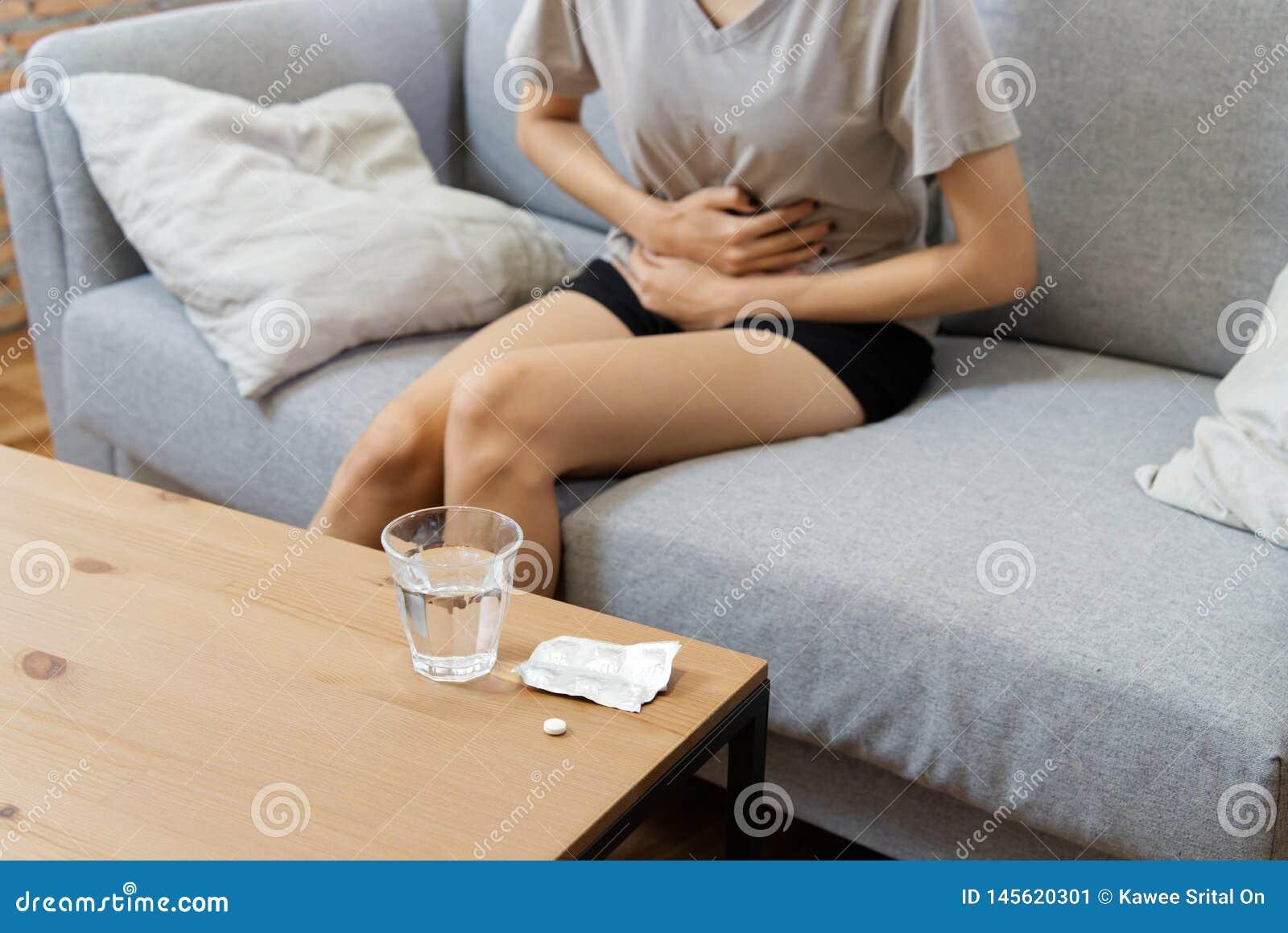 Jeunes femmes asiatiques sur la douleur de sofa du mal de ventre et avoir une certaine fièvre en raison des règles