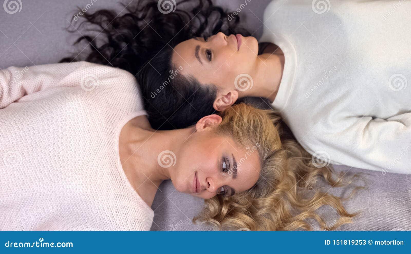 Jeunes femmes attirantes avec de beaux longs cheveux se trouvant sur le plancher, séance photos