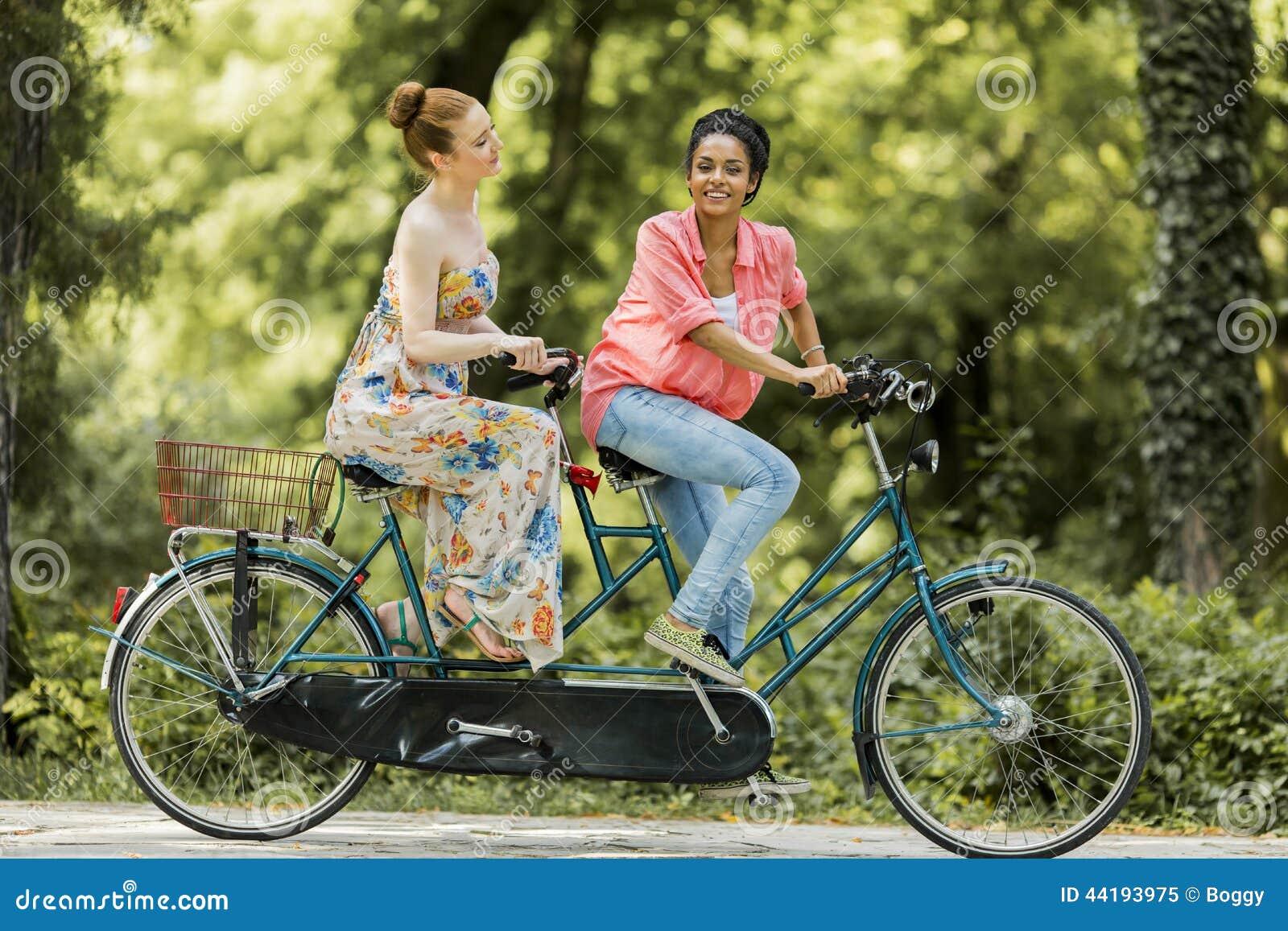 Jeunes femmes montant sur la bicyclette tandem