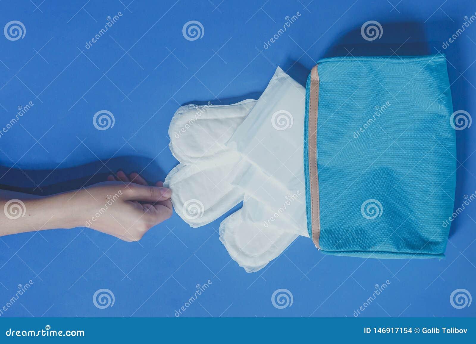 Jeunes femmes prenant les protections sanitaires à l intérieur de son sac cosmétique sur le fond bleu