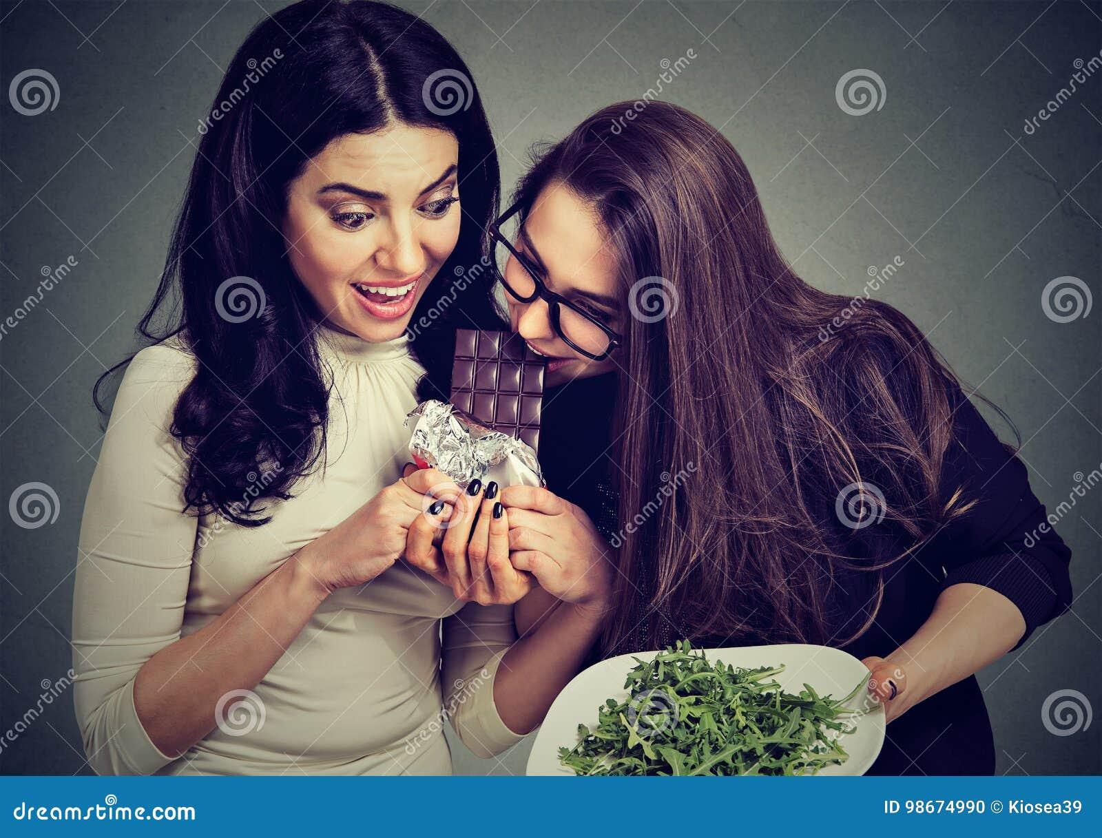 Jeunes femmes suivantes un régime avec de la salade verte mourant d envie d un chocolat sucré