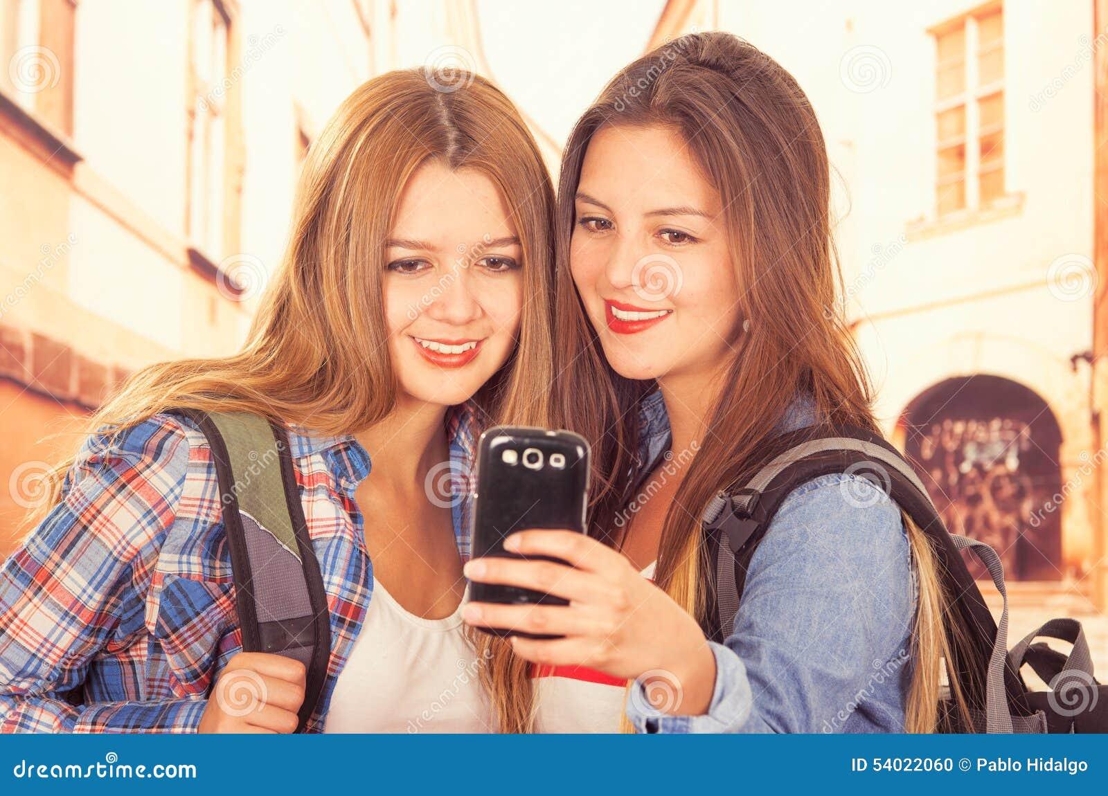 Jeunes filles à la mode mignonnes à l aide du téléphone portable