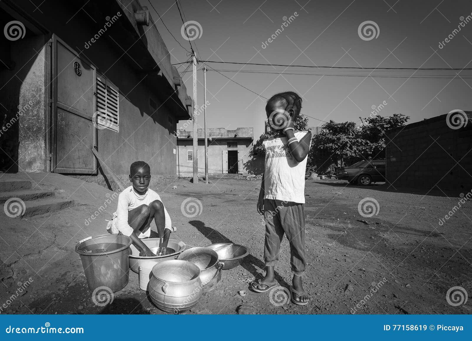 Jeunes filles africaines faisant la vaisselle dans la rue de Bamako i
