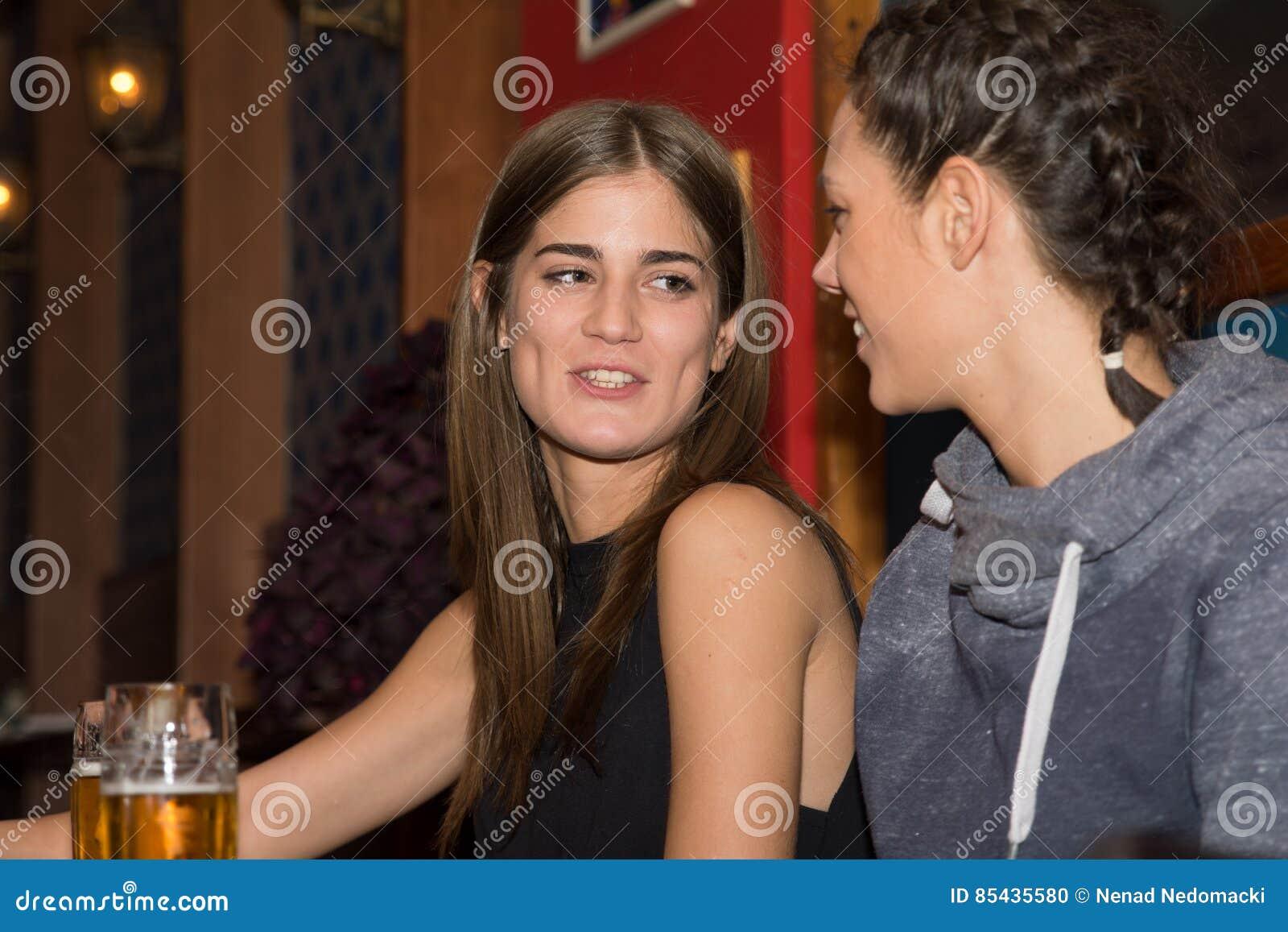 Jeunes filles buvant et ayant l amusement ensemble
