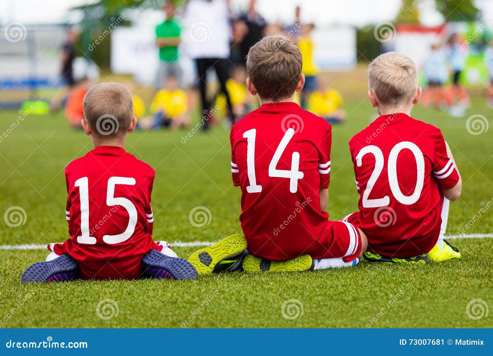 Jeunes garçons dans l équipe de football s asseyant ensemble sur le champ de sports