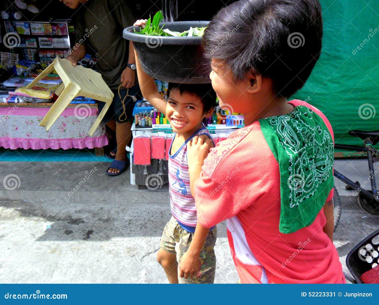 Jeunes garçons sur un marché du cainta, rizal, Philippines vendant des fruits et légumes