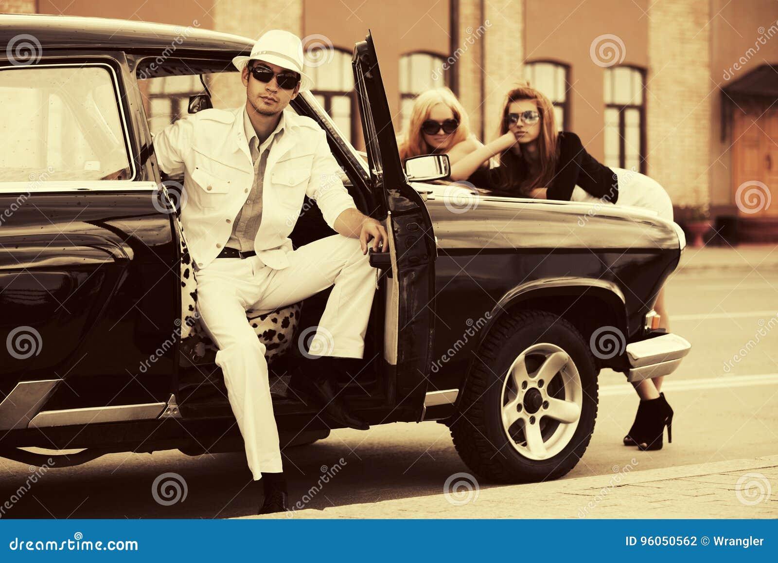 Jeunes homme et femmes heureux de mode en la voiture de vintage