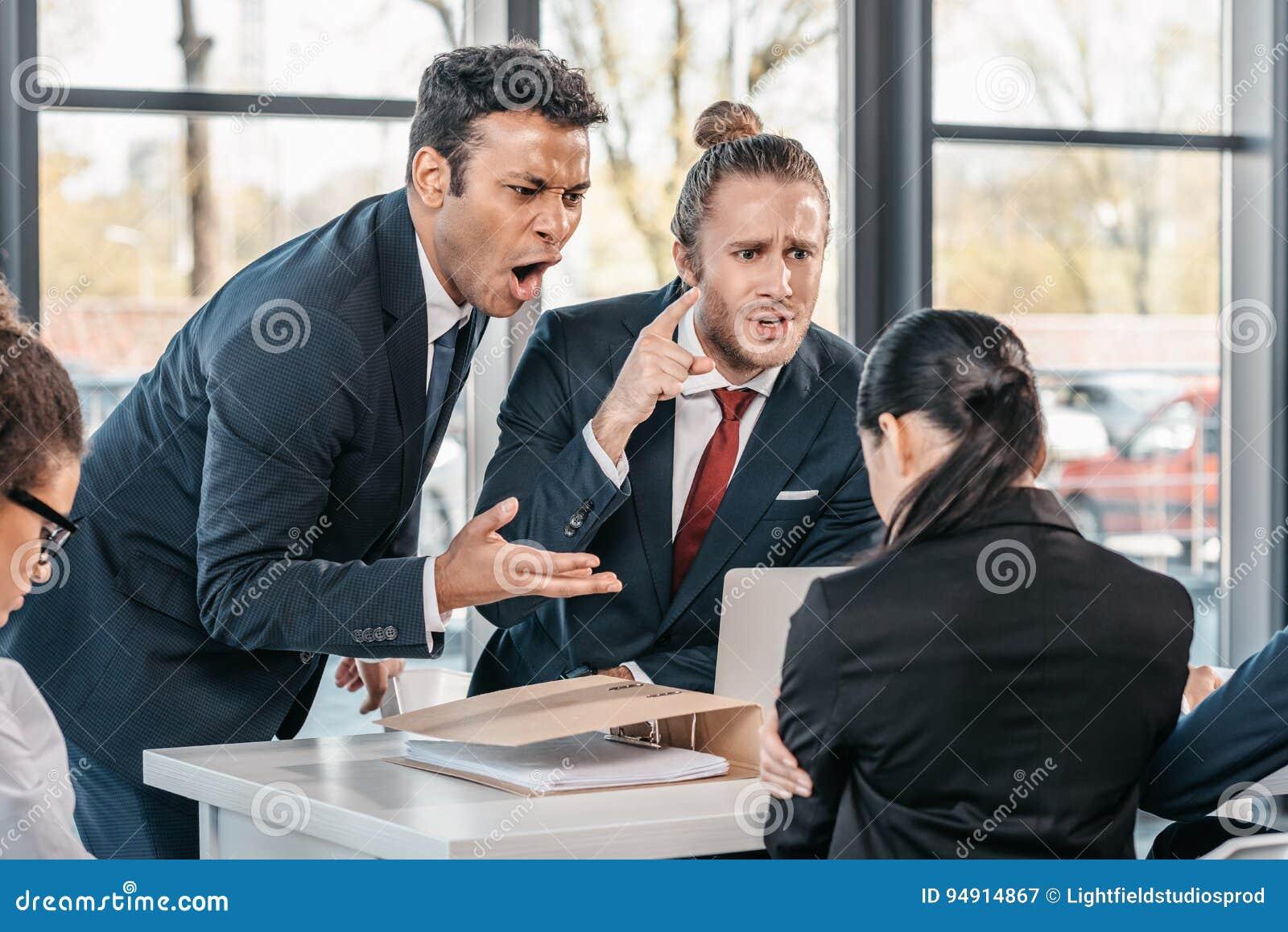 Jeunes hommes daffaires émotifs dans le formalwear discutant lors
