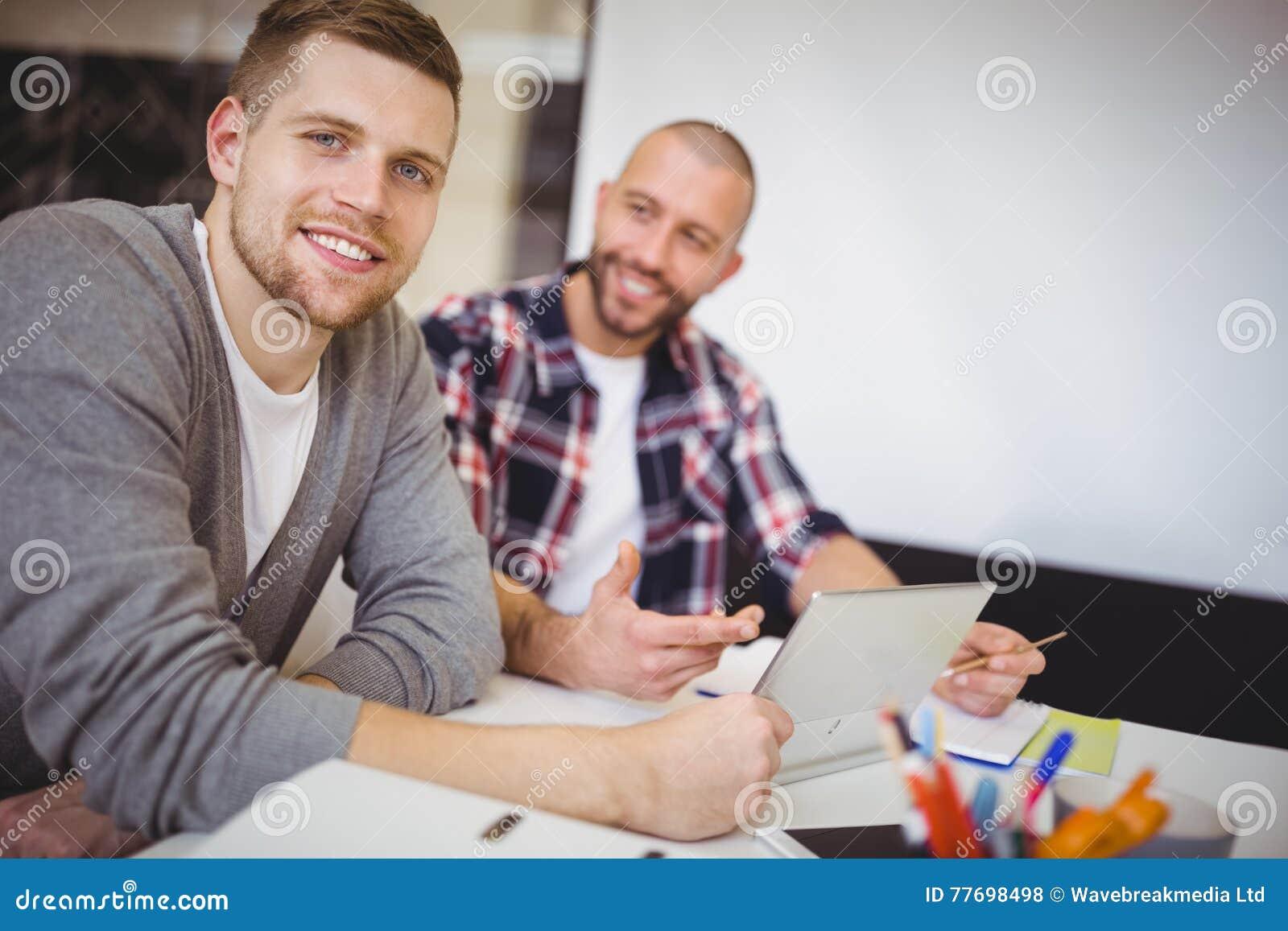 Jeunes hommes d affaires utilisant le comprimé numérique au bureau
