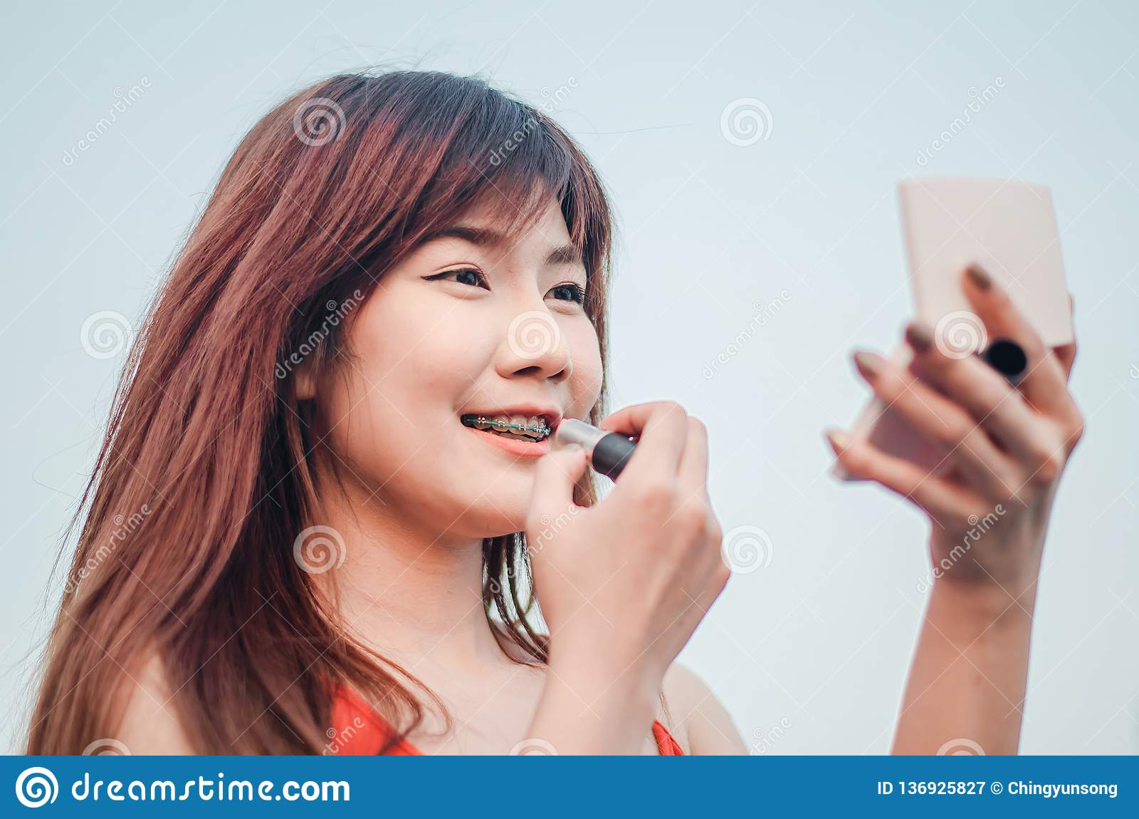 Jeunes lèvres de dessin de sourire de femme d affaires avec le rouge à lèvres se tenant dehors au-dessus de la ville