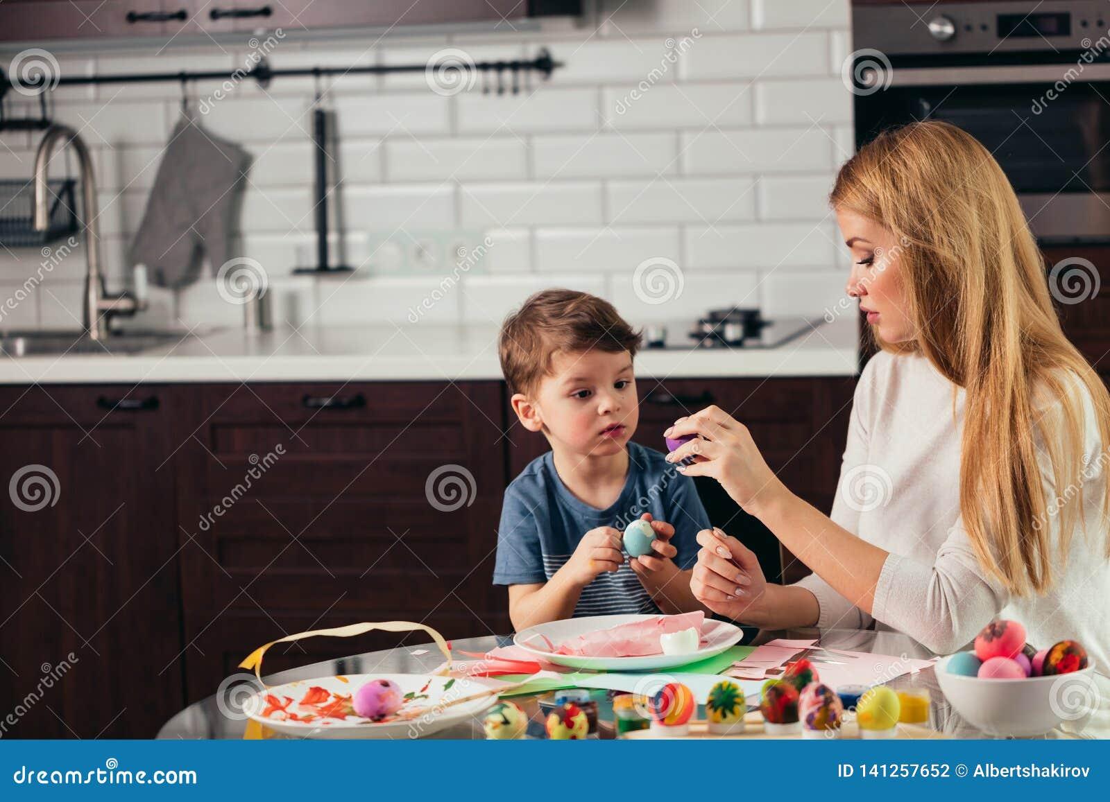 Jeunes mère heureuse et fils mangeant ensemble les oeufs de pâques faits maison