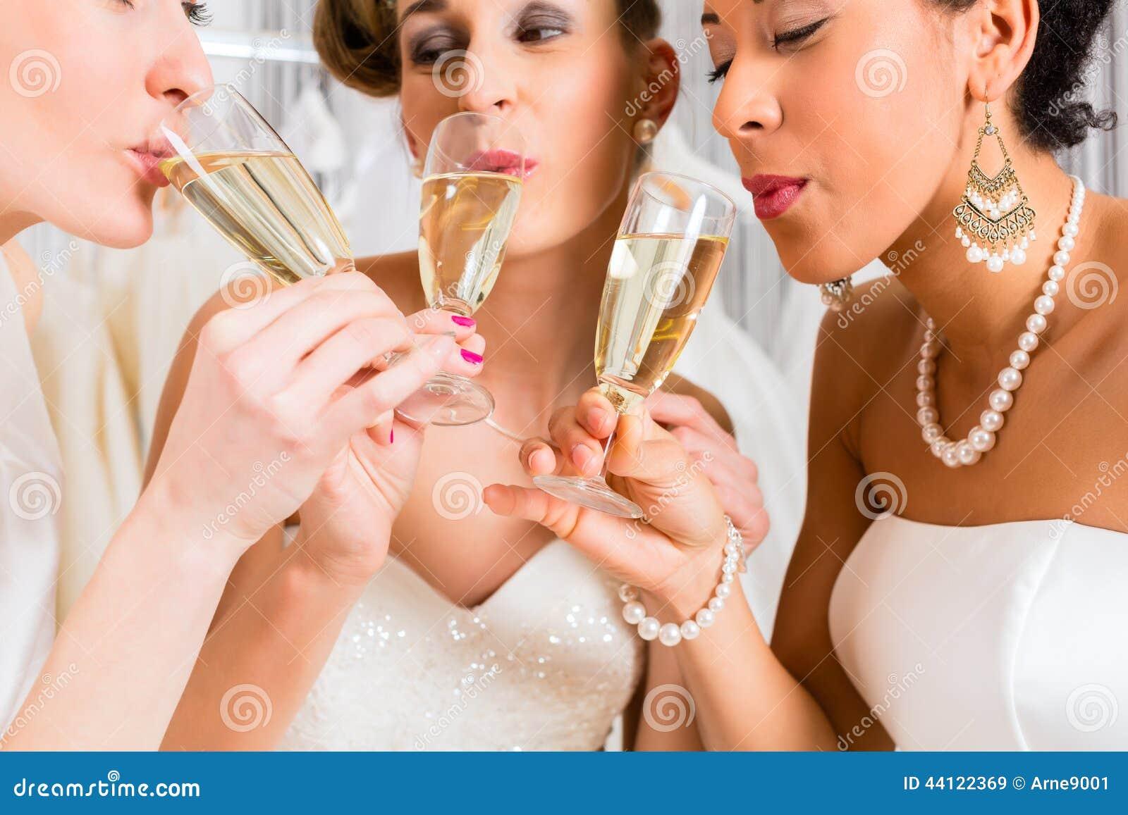 Jeunes mariées buvant du champagne dans la boutique de mariage