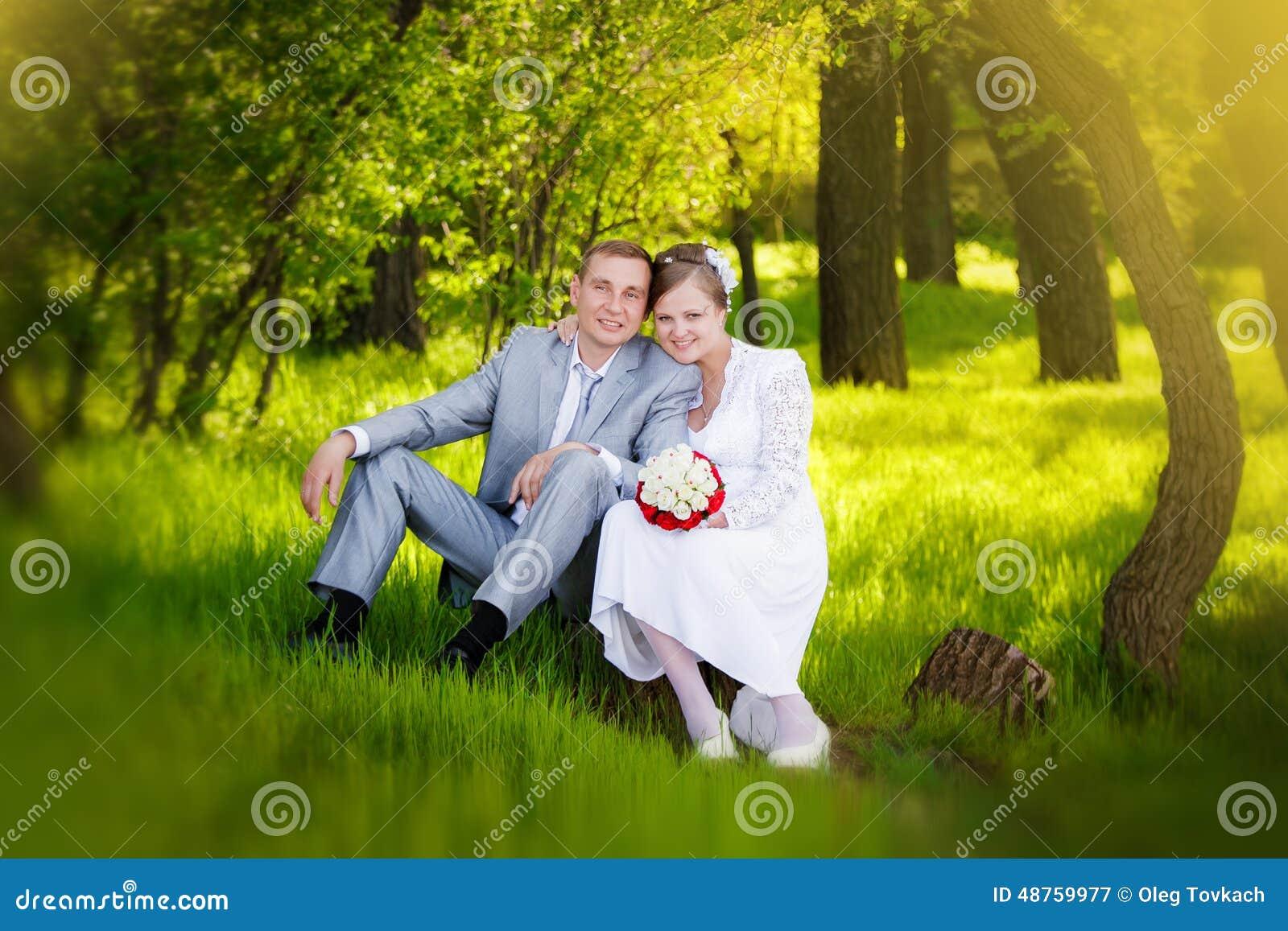 Jeunes mariés étreignant et regardant aux yeux d une une autre séance une herbe verte