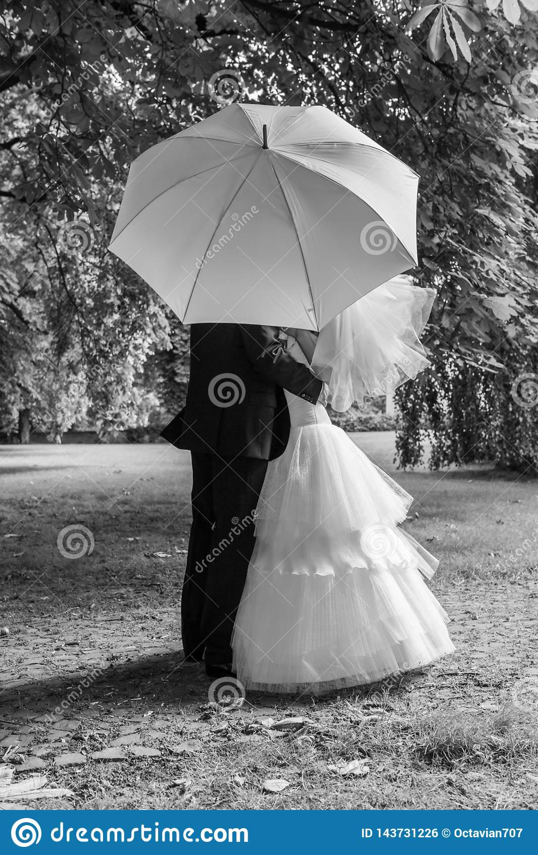 Jeunes mariés avec le parapluie blanc