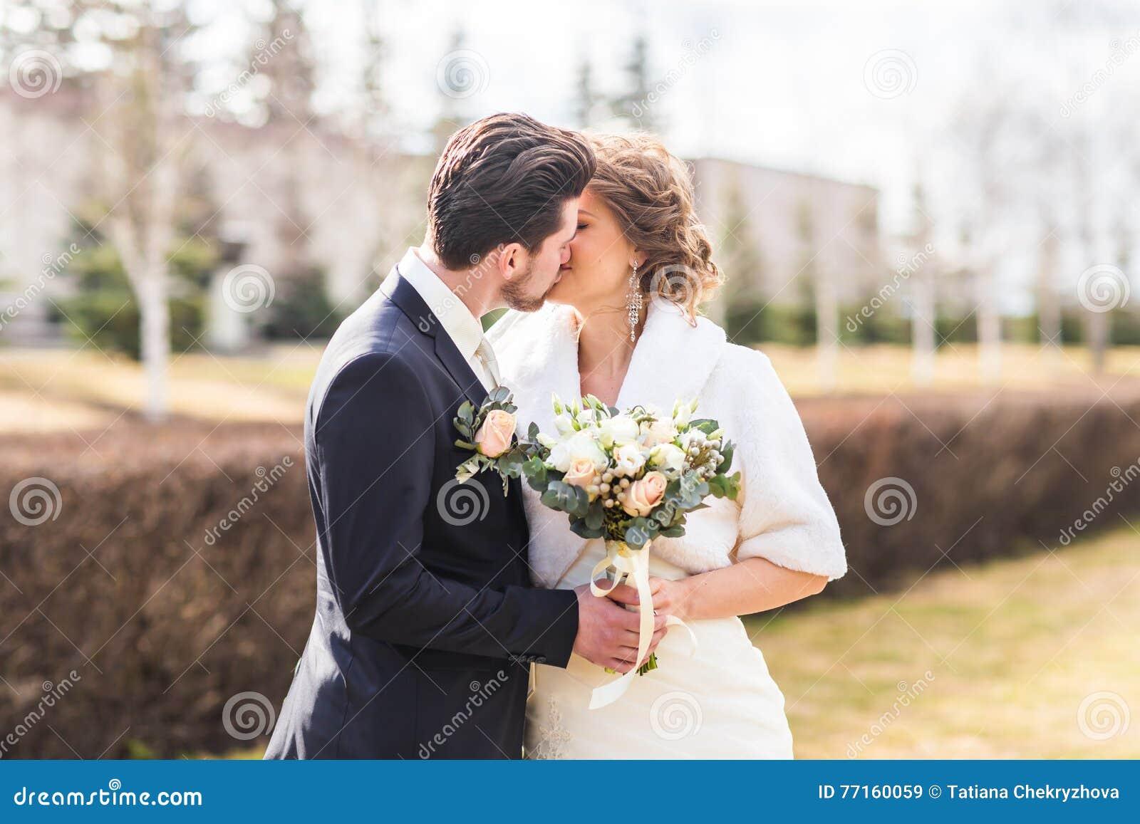 Jeunes mariés embrassant leur jour du mariage dehors