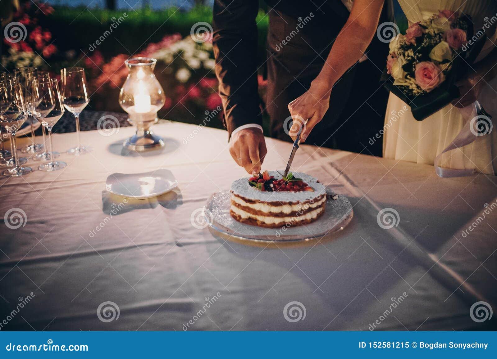 Jeunes mariés heureux élégants coupant le gâteau l épousant ensemble avec des fruits à l extérieur de réception de mariage le soi