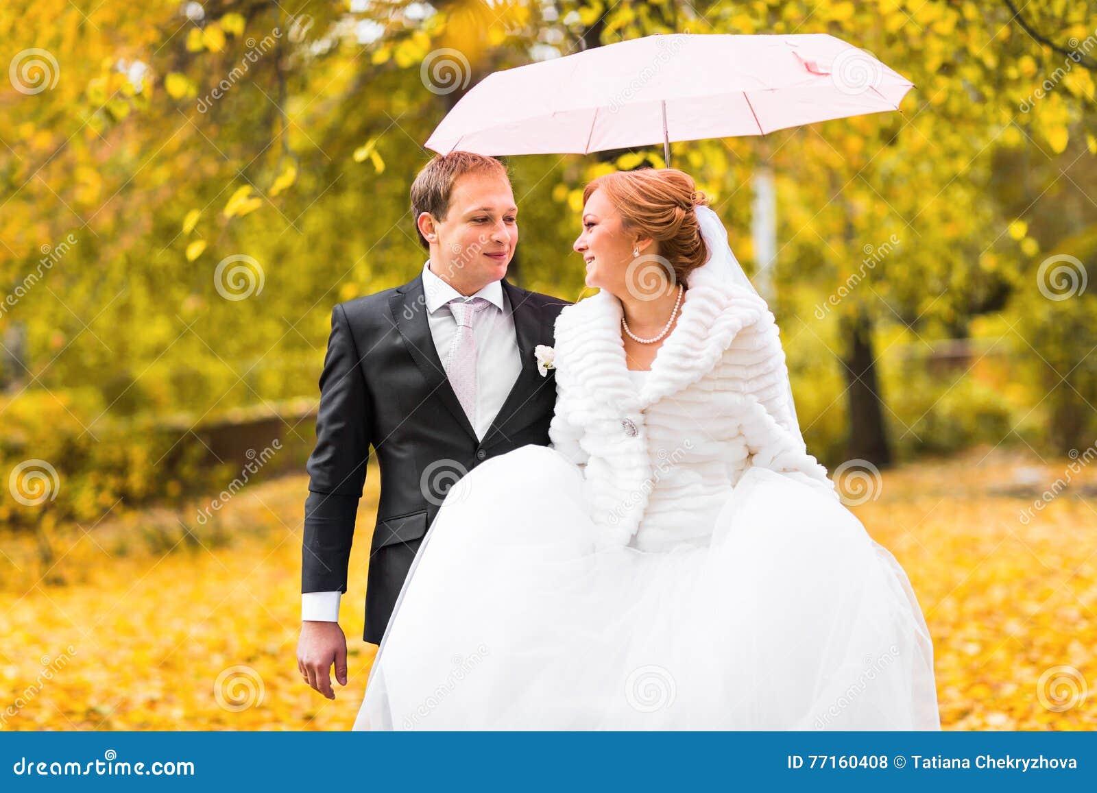 Jeunes mariés marchant en parc d automne