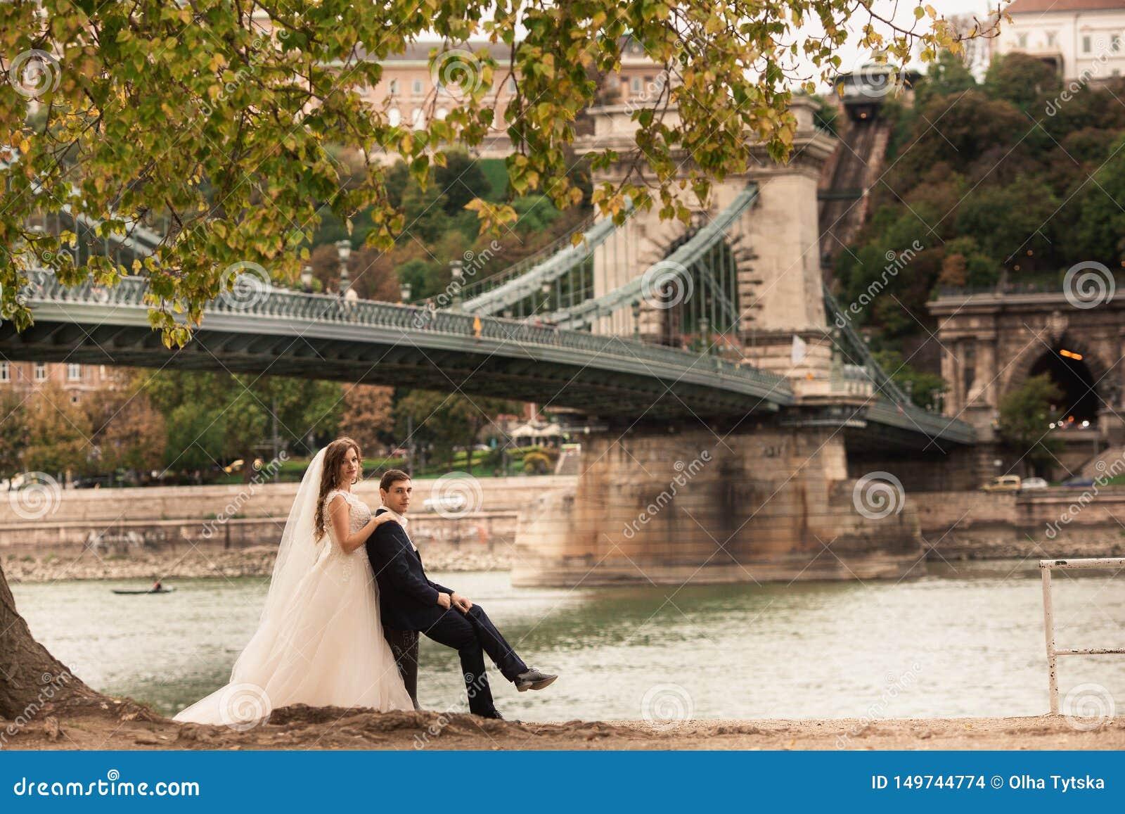 Jeunes mariés près du pont à Budapest Couples magnifiques de mariage marchant dans la vieille ville de Budapest