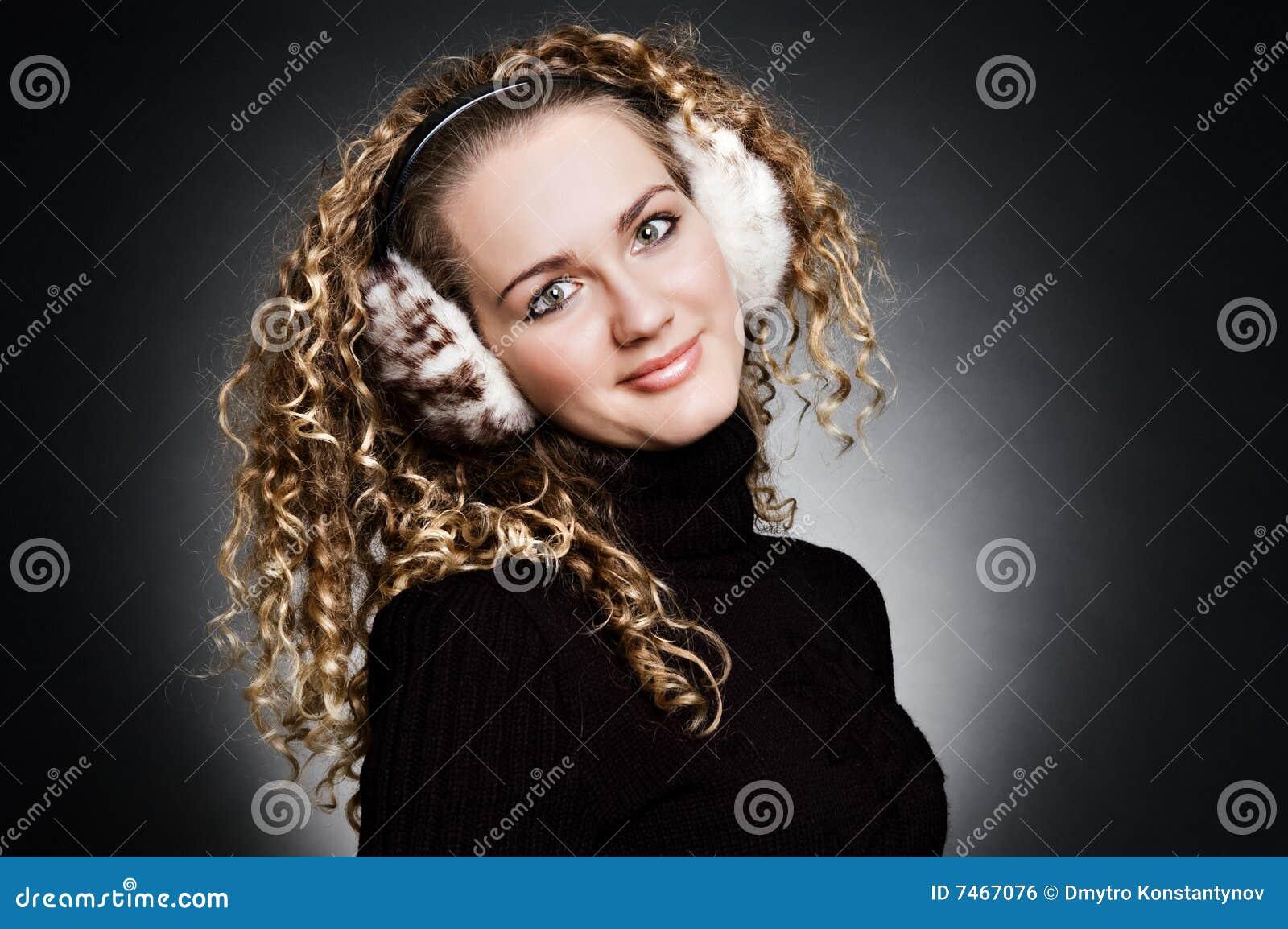 Jeunes souriants d écouteurs de fille de fourrure