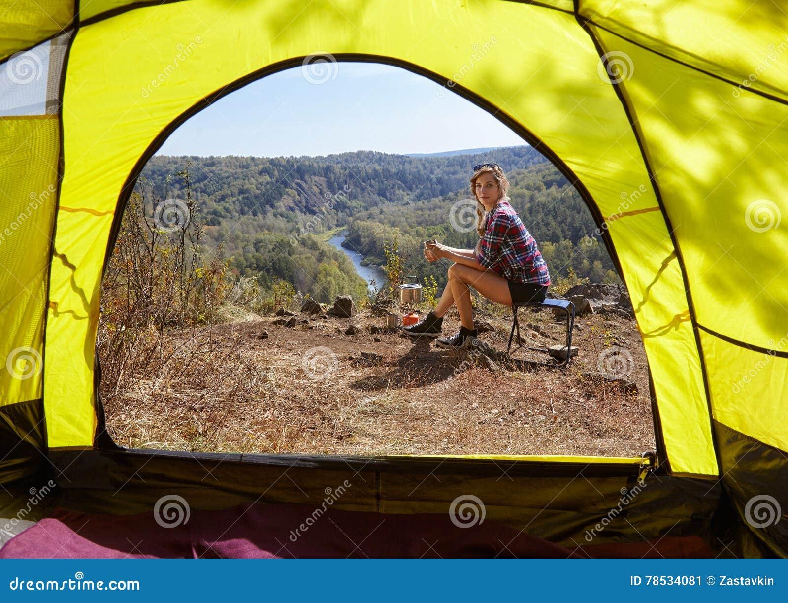 Jeunes touristes blondes de femme dans le camp sur la falaise au-dessus de la rivière et antérieur