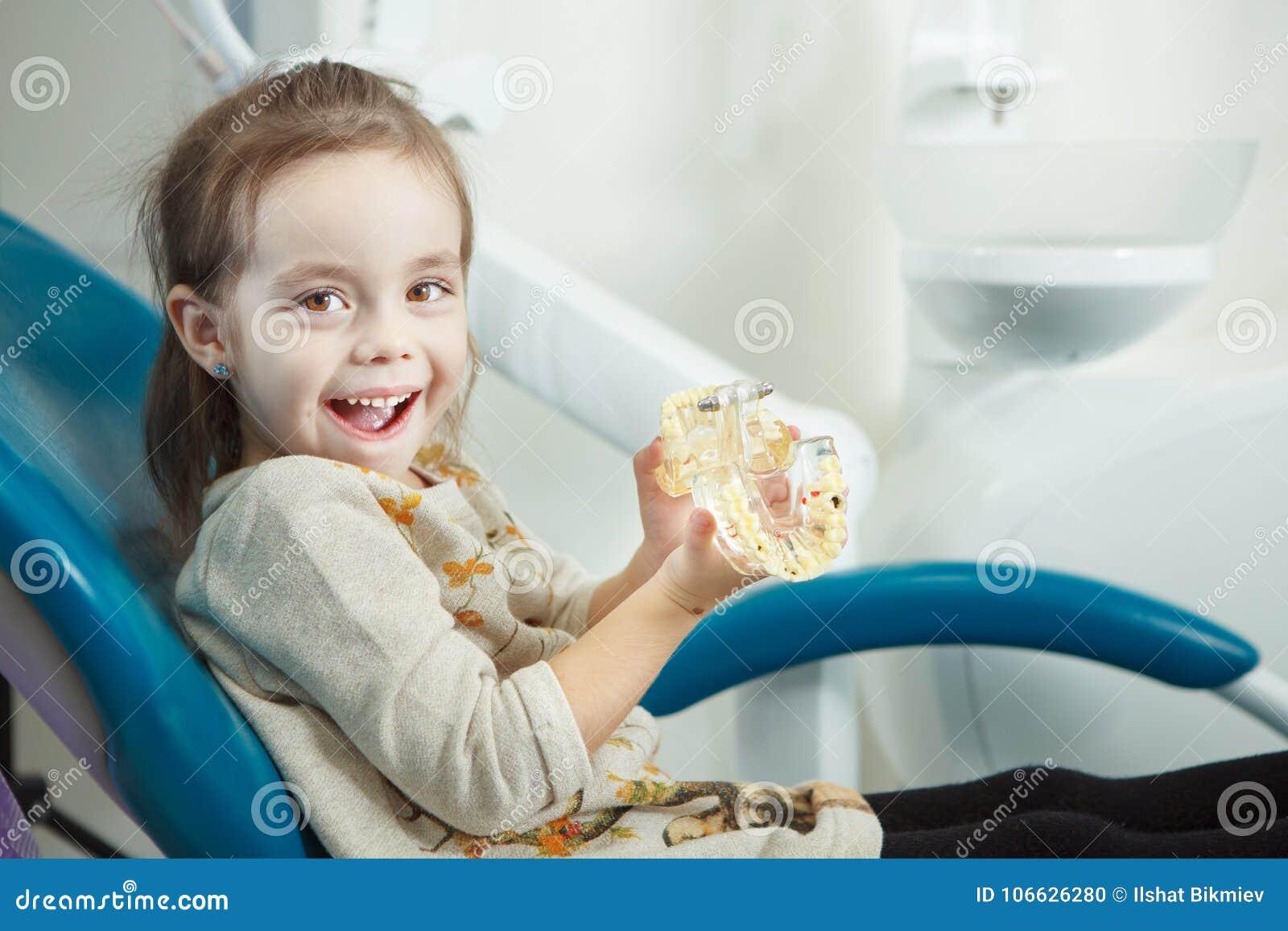 Jeux d enfant avec la mâchoire humaine artificielle dans la chaise de dentiste