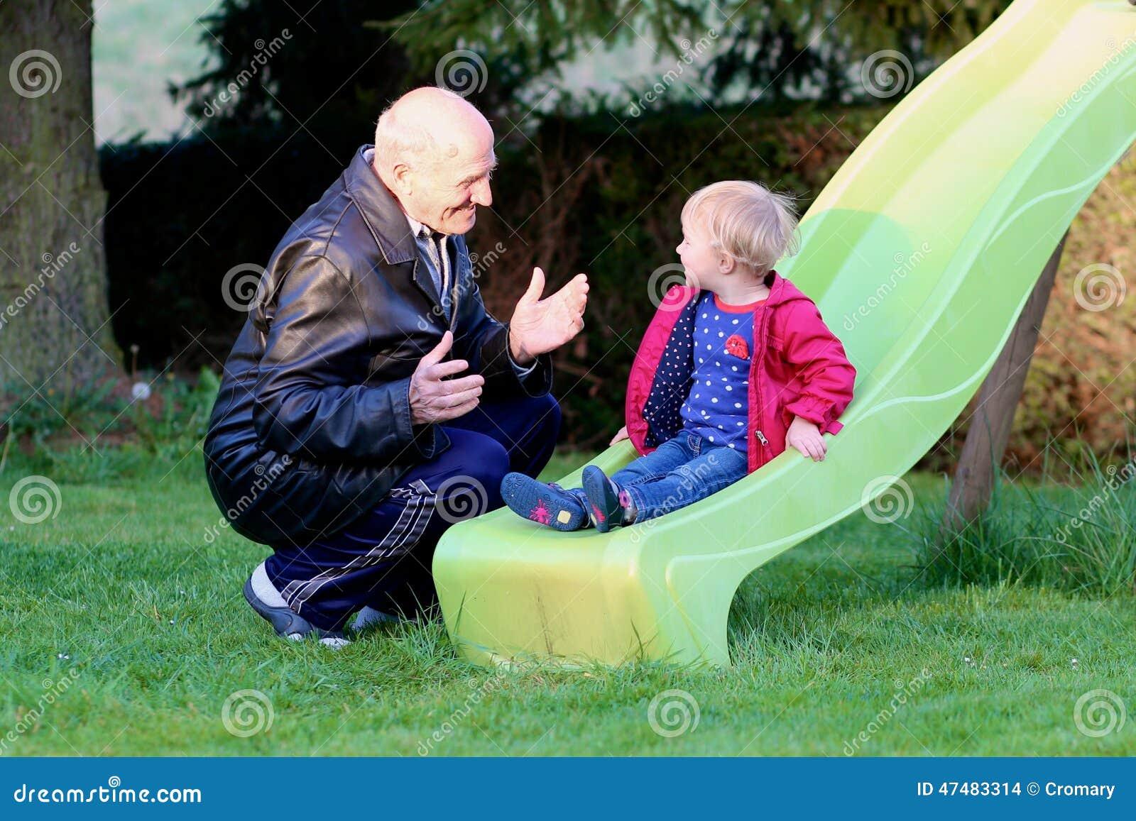 jeux de grand p re avec la petite fille sur le terrain de jeu photo stock image 47483314. Black Bedroom Furniture Sets. Home Design Ideas