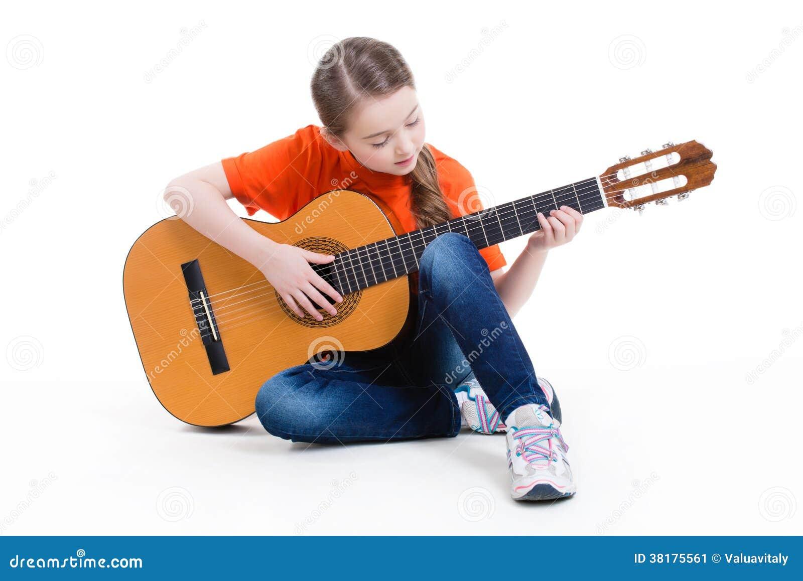 Jeux mignons de fille sur la guitare acoustique.