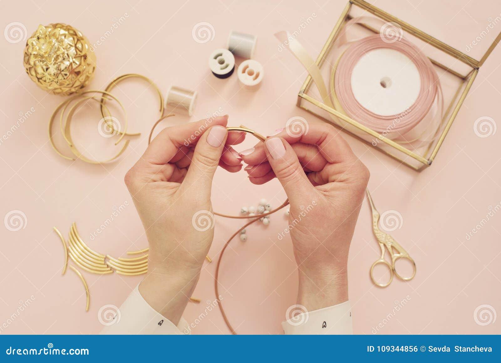Jewelry designer workplace. Woman hands making handmade jewelry. Freelance fashion femininity workspace in flat lay style. Pastel