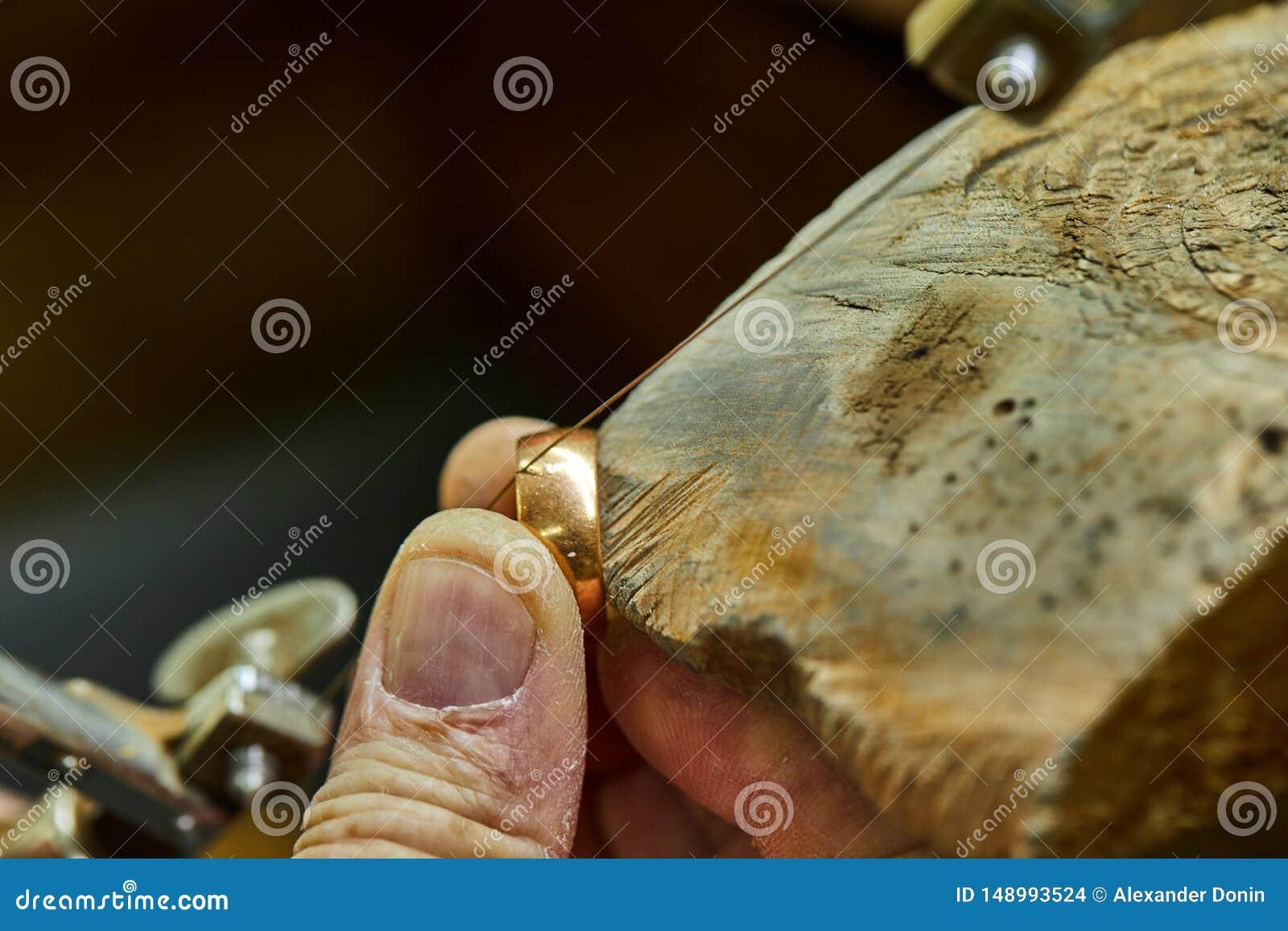 Jewelry production. Jeweler using saw to create jewelry
